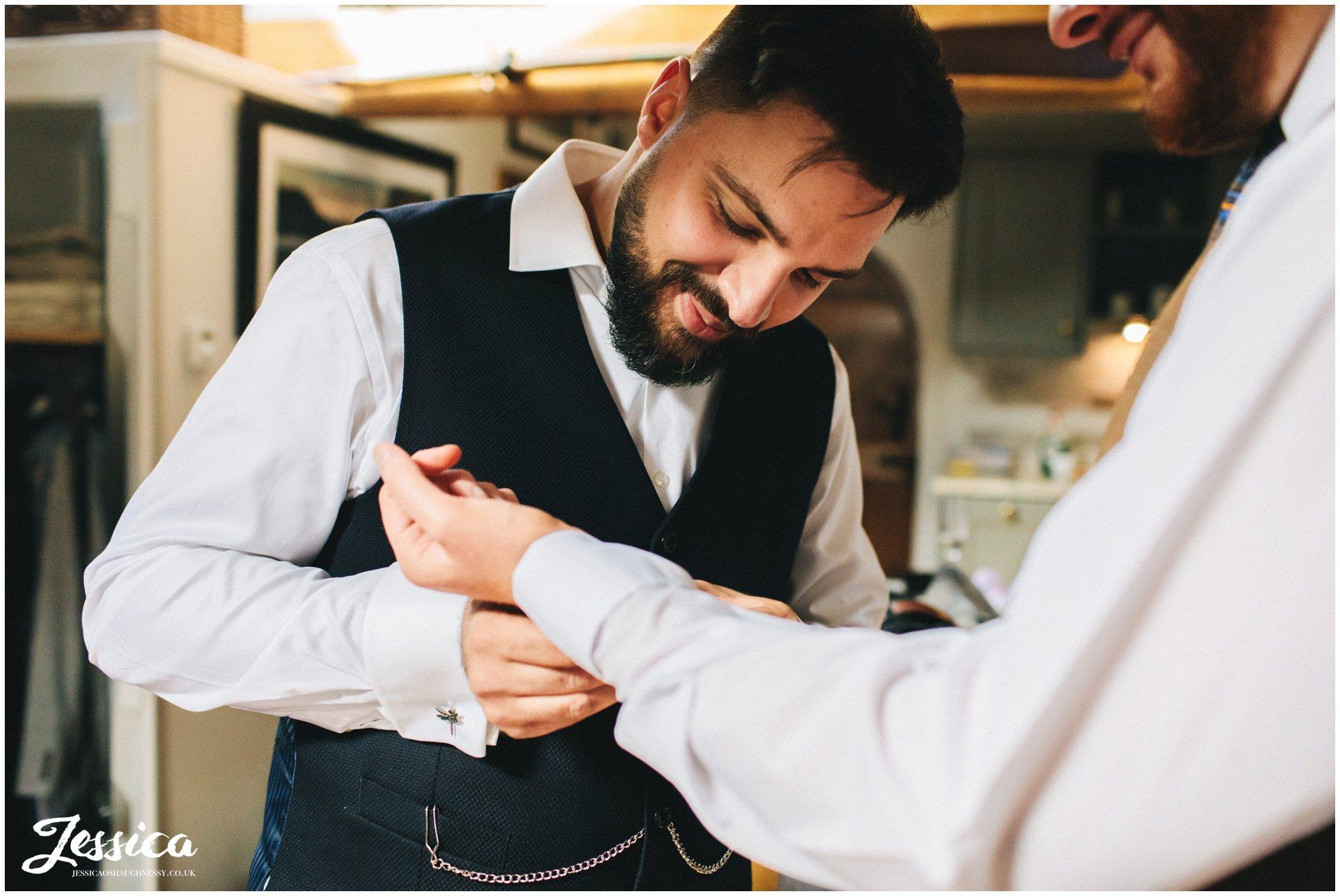 Groom fastens his fiance's cufflinks