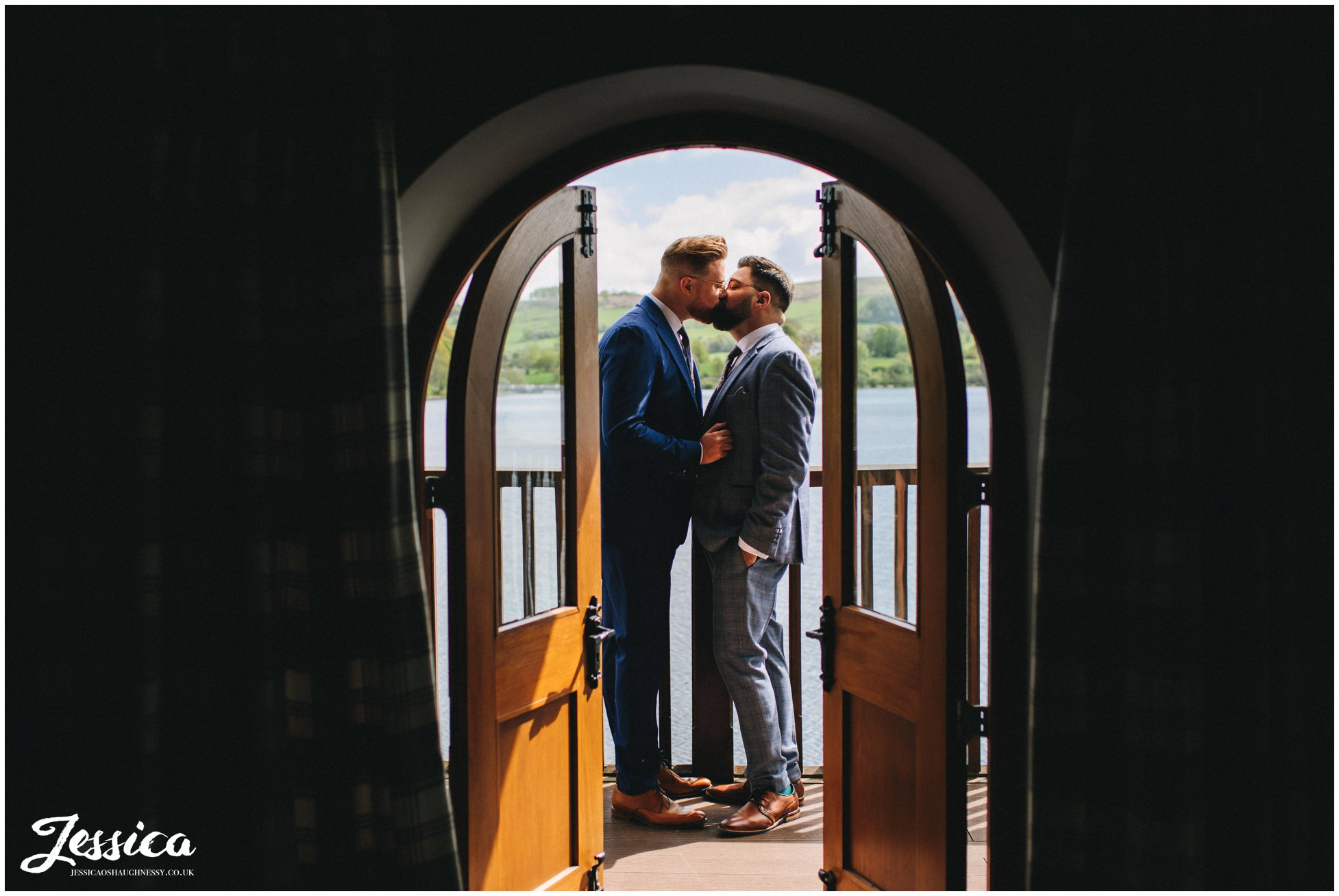 The grooms kiss on the balcony of the boathouse, ullswater