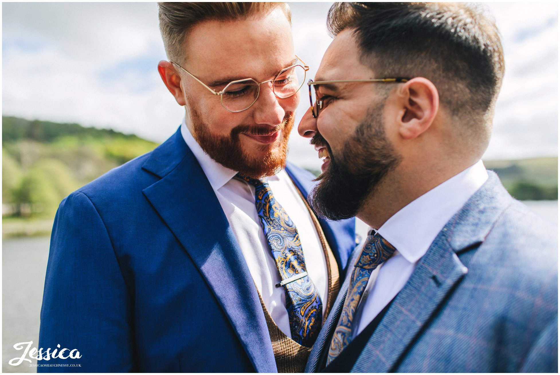 the grooms have photographs taken on the jetty at the boathouse
