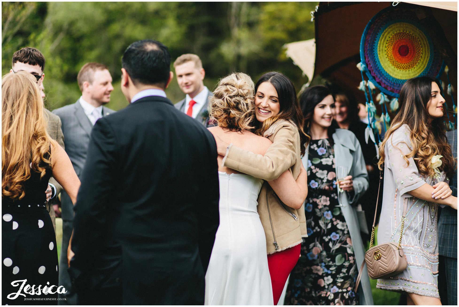 guests hugging as they arrive for the same sex tipi wedding