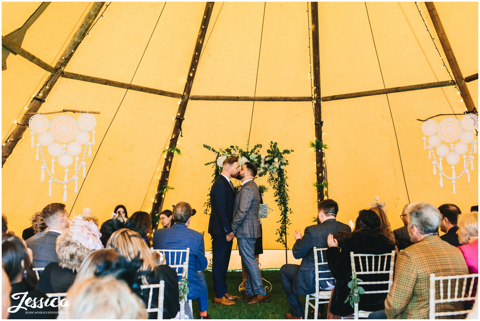 the grooms share their first kiss at the lake district wedding