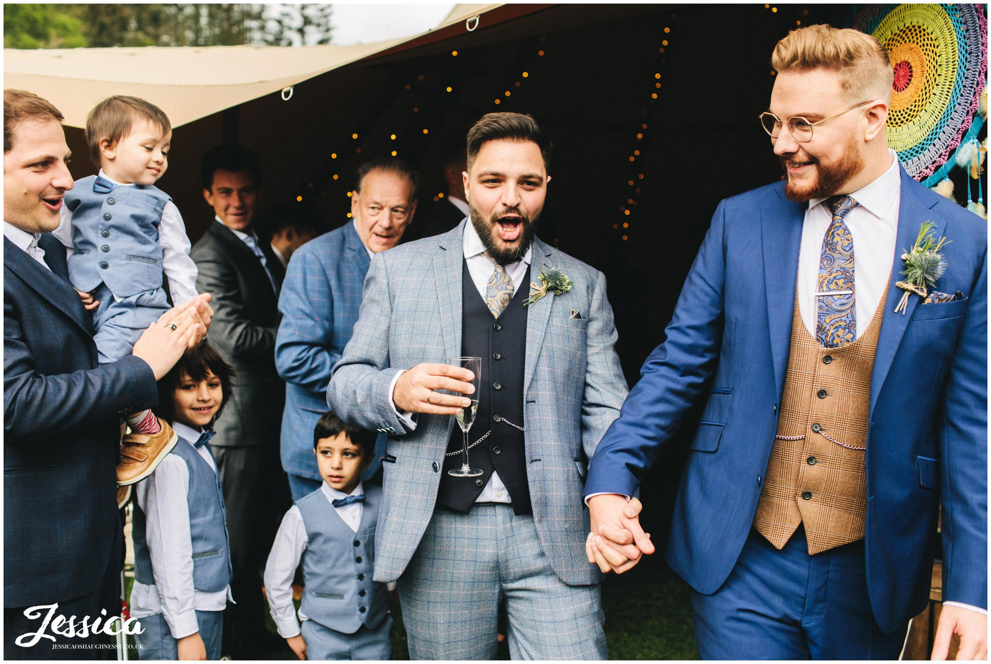 Grooms cheer as they walk down the aisle as a married couple