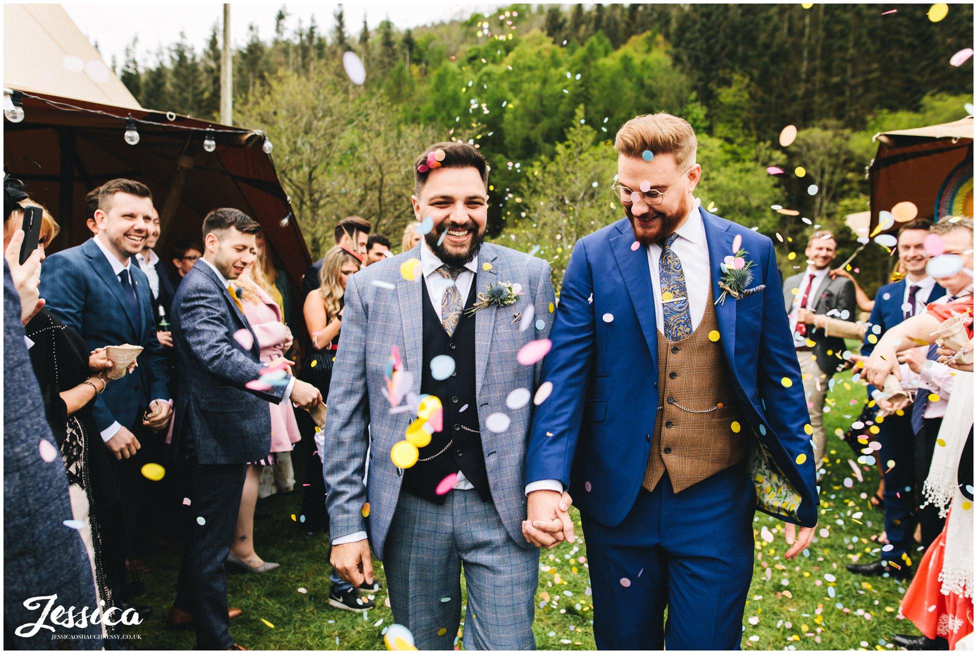 groom & groom walk through their confetti line