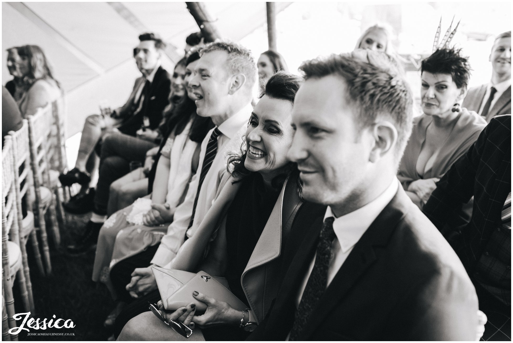 wedding guests enjoy the speeches during the tipi ceremony
