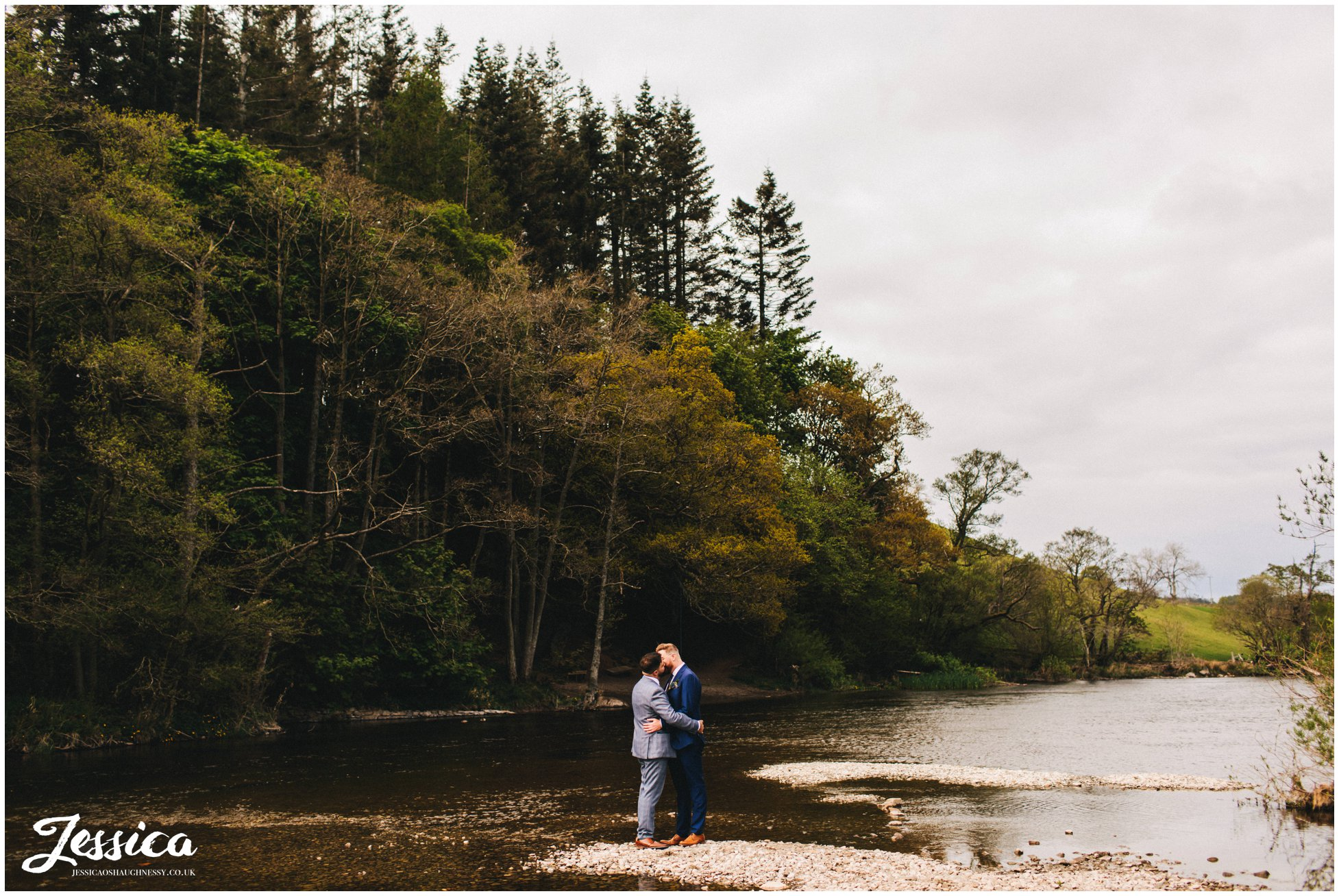 the couple share a kiss down by the river in pooley bridge