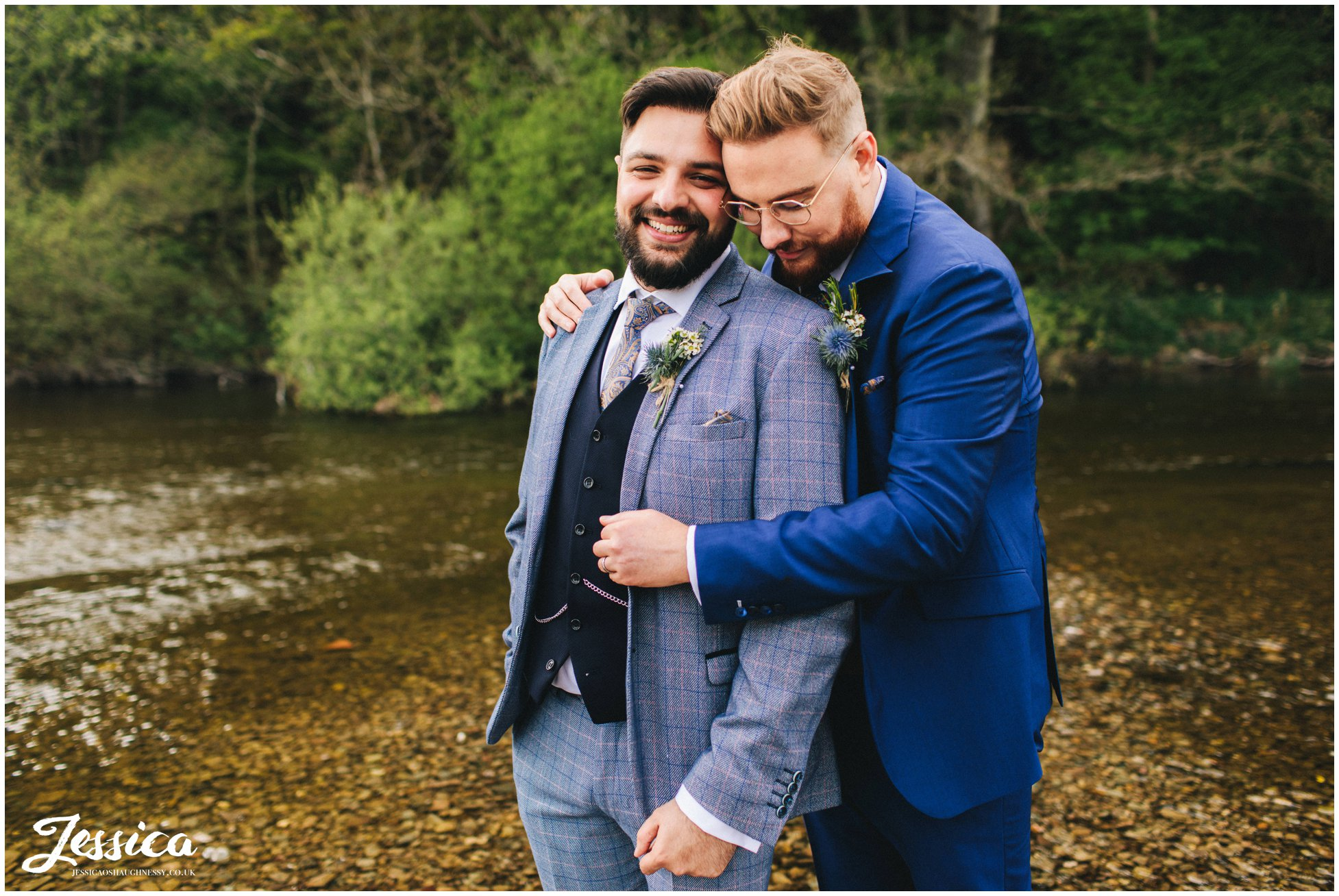 the couple embrace by the river at their lake district wedding