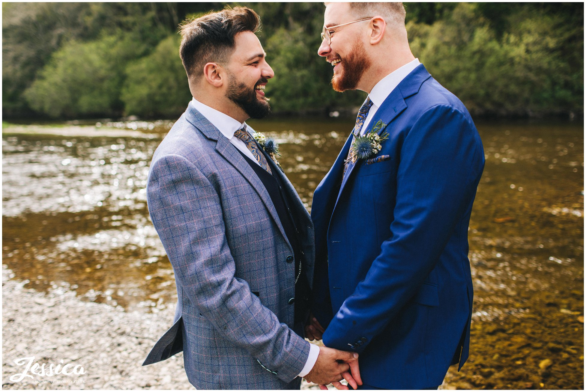 the grooms hold hands down by the river