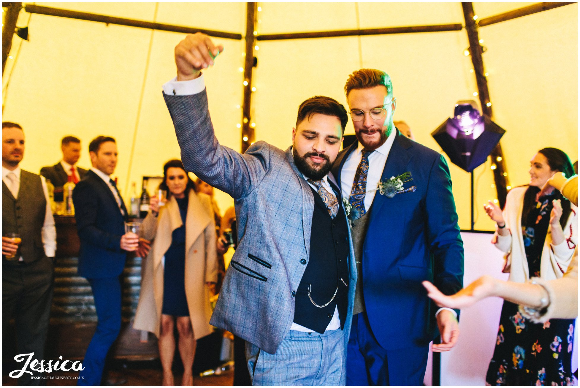 the grooms dance in the tipi as guests cheer them on
