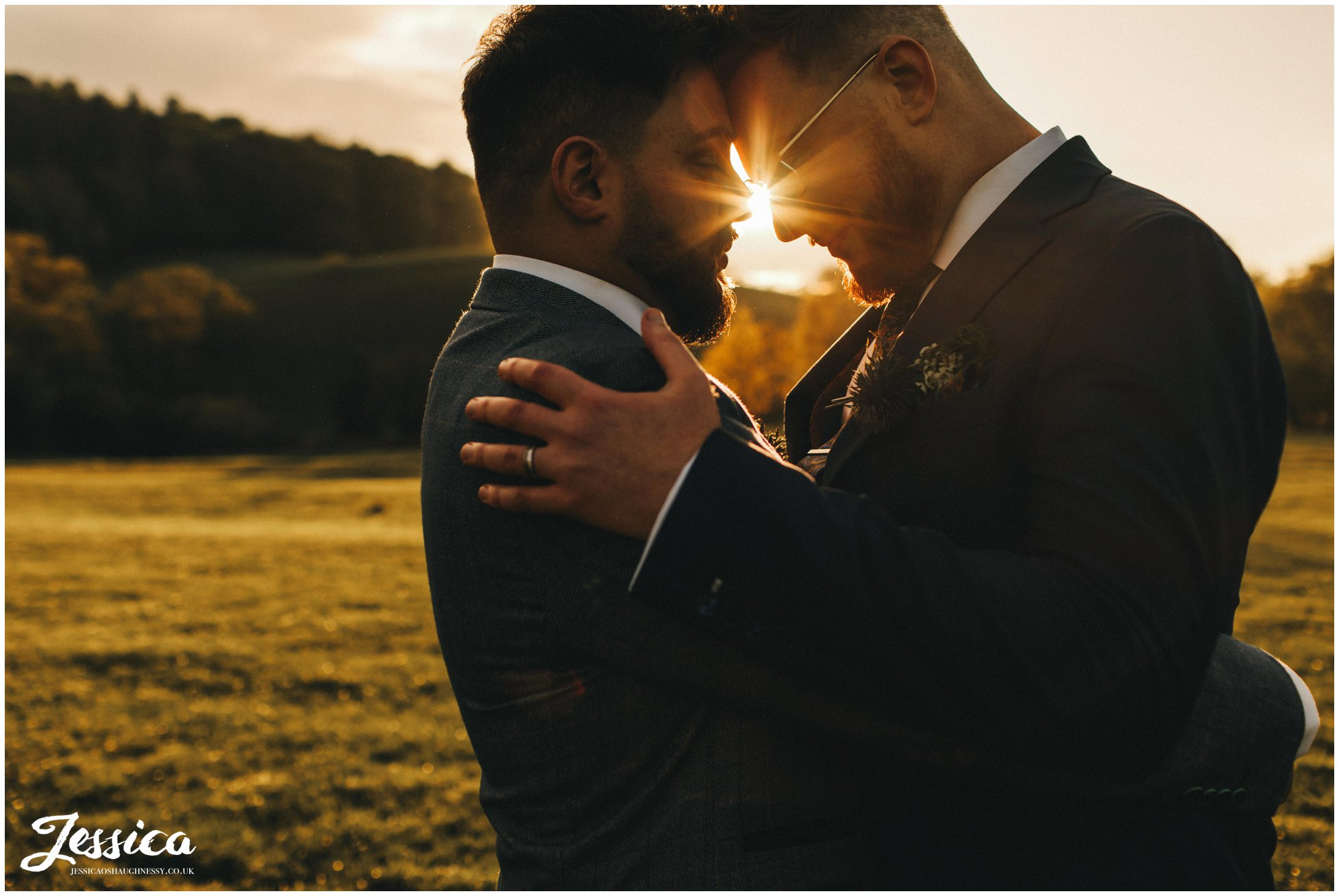 the grooms hold each other in the golden evening light