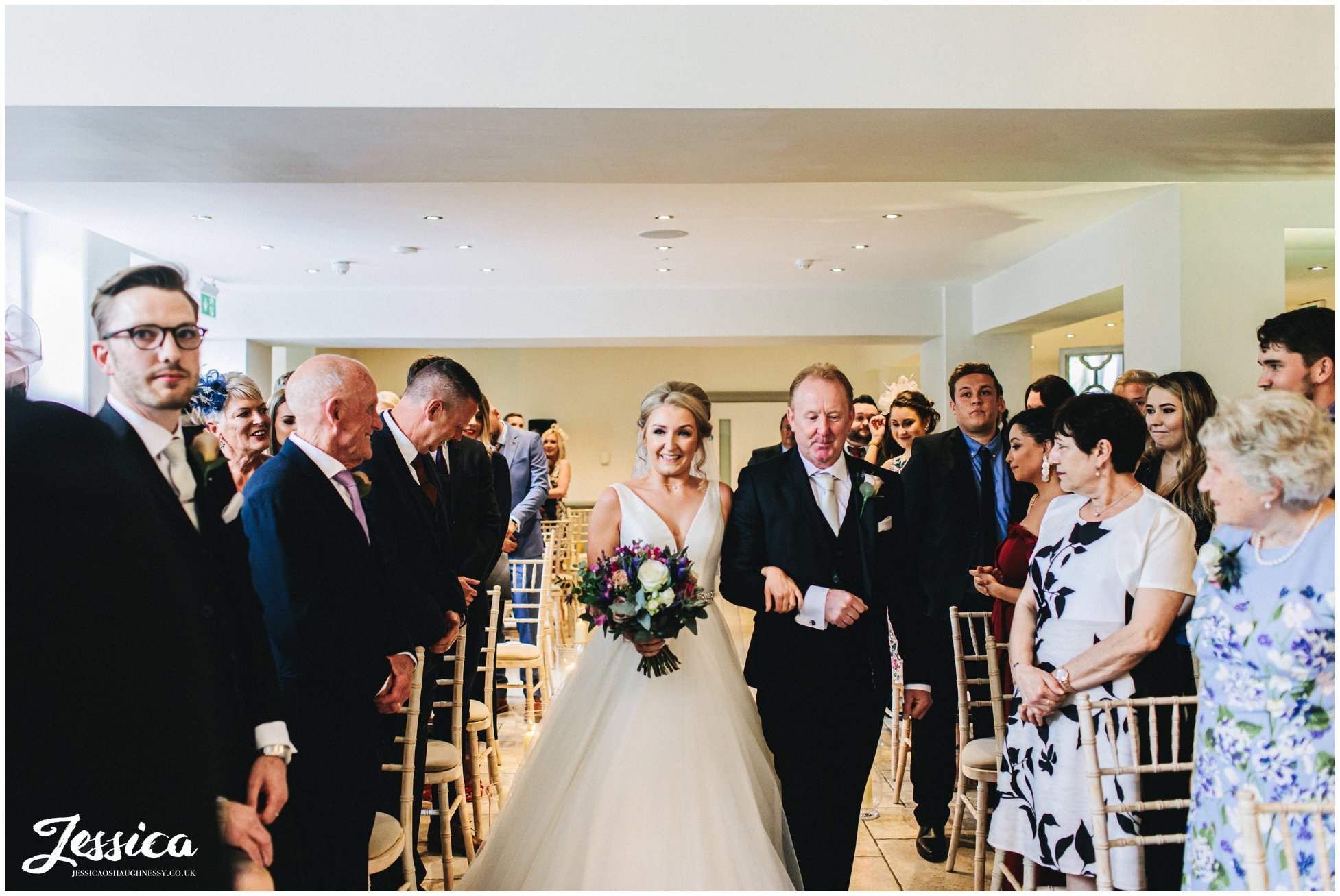bride walks down the aisle at tyn dwr hall