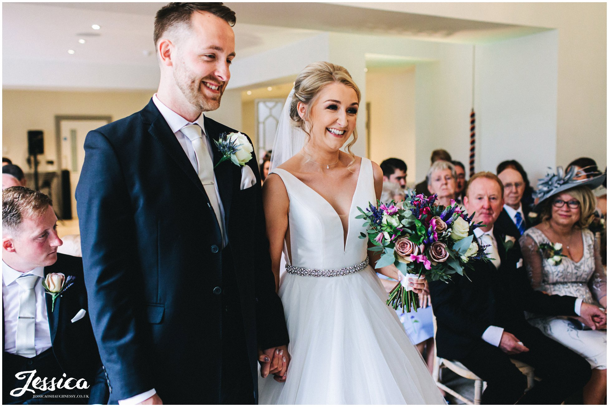 bride and groom smile during wedding ceremony in north wales