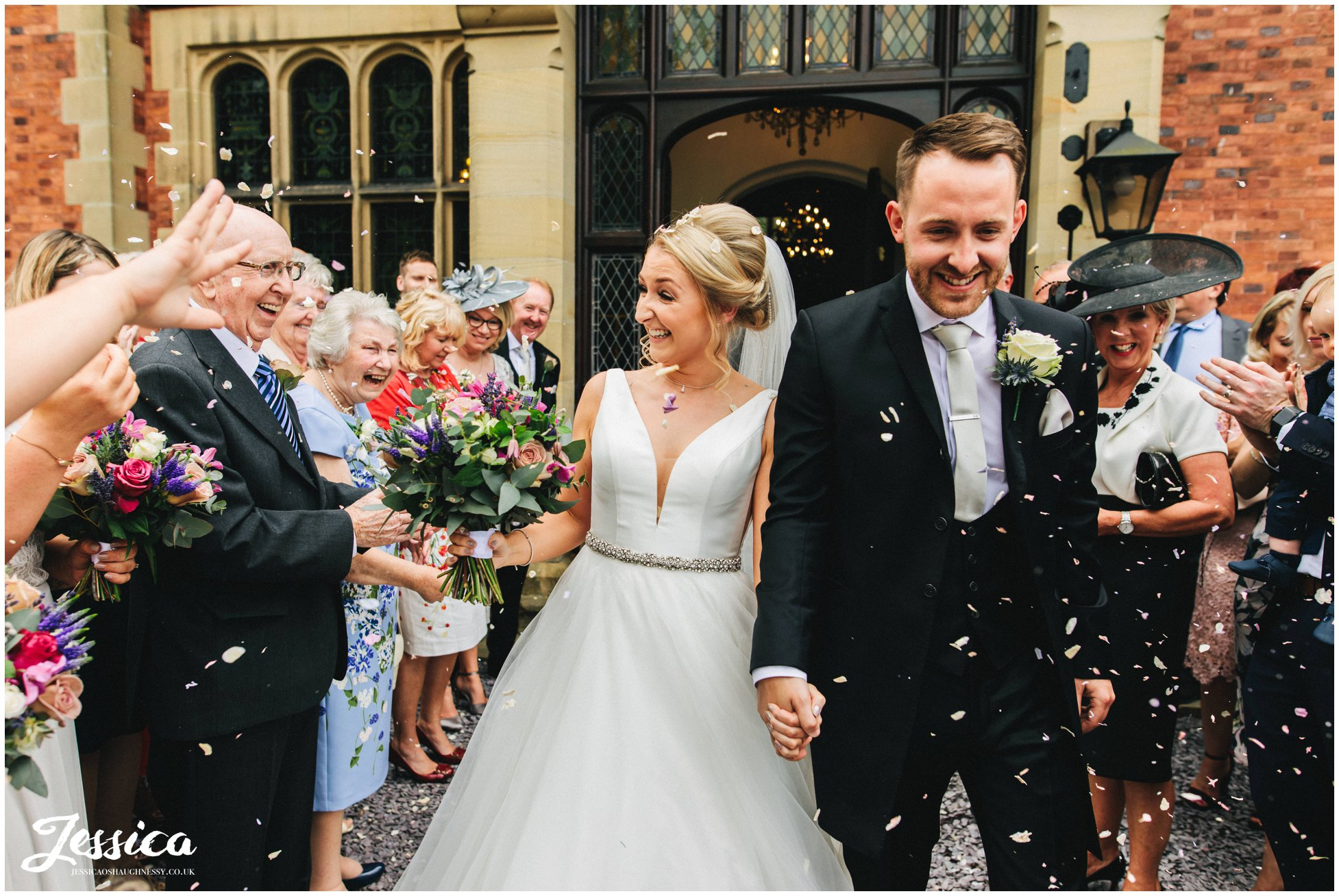 guests throw confetti over the couple
