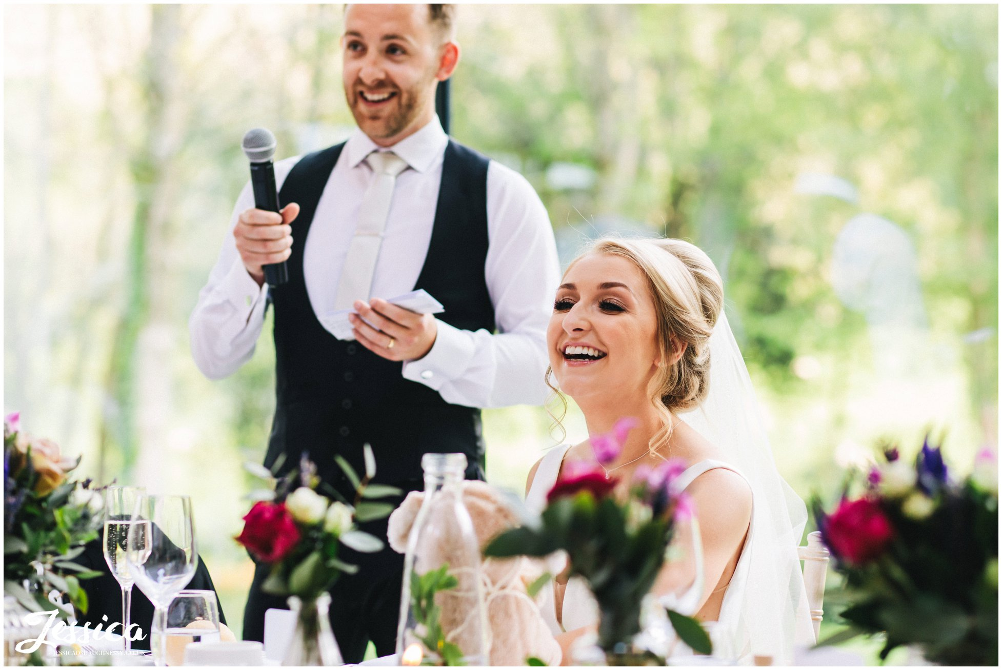 bride laughs as her new husband gives his speech at tyn dwr hall