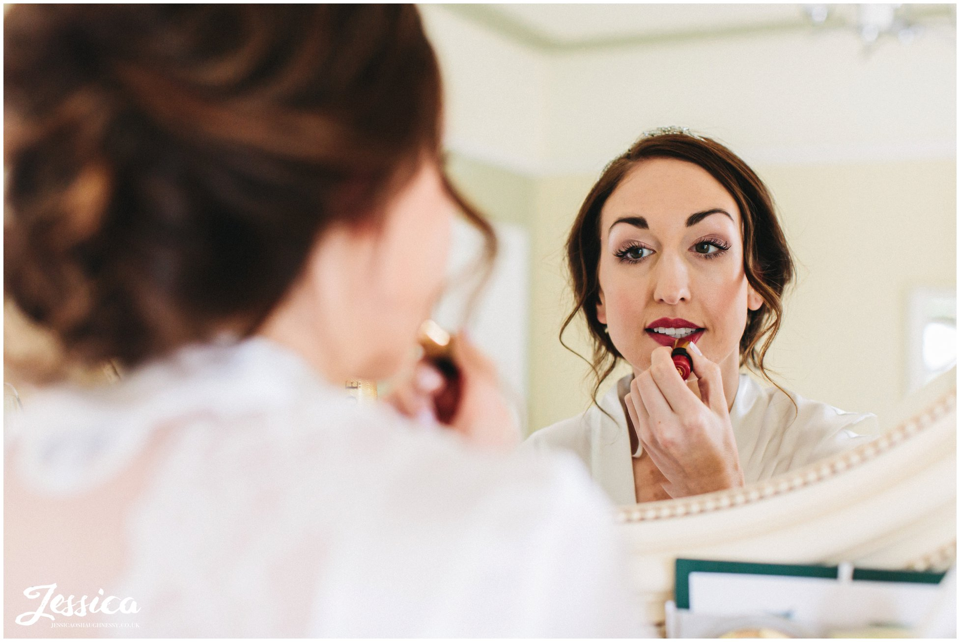 the bride applies red lipstick in the mirror