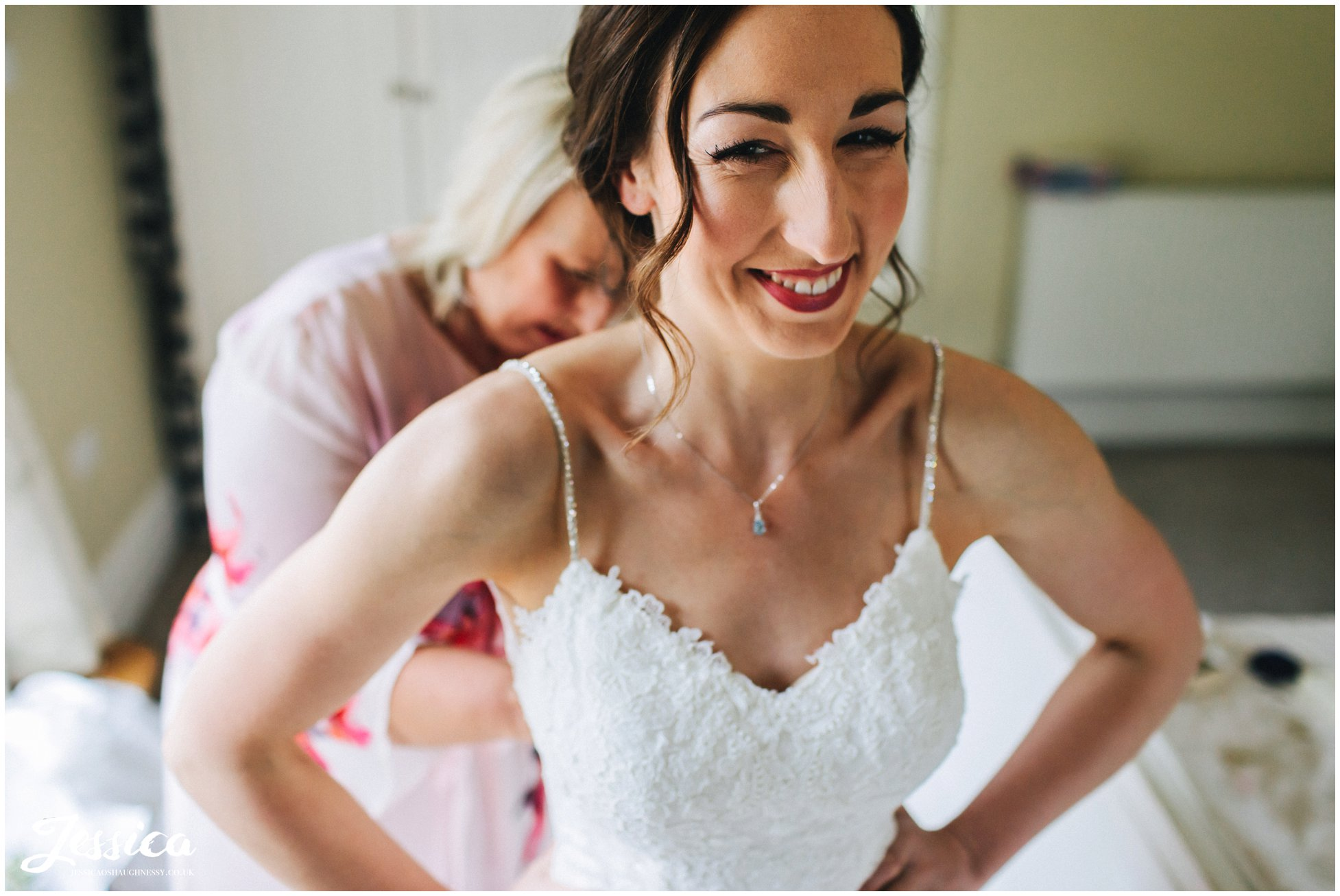 bride gets into her wedding dress with her from her mother