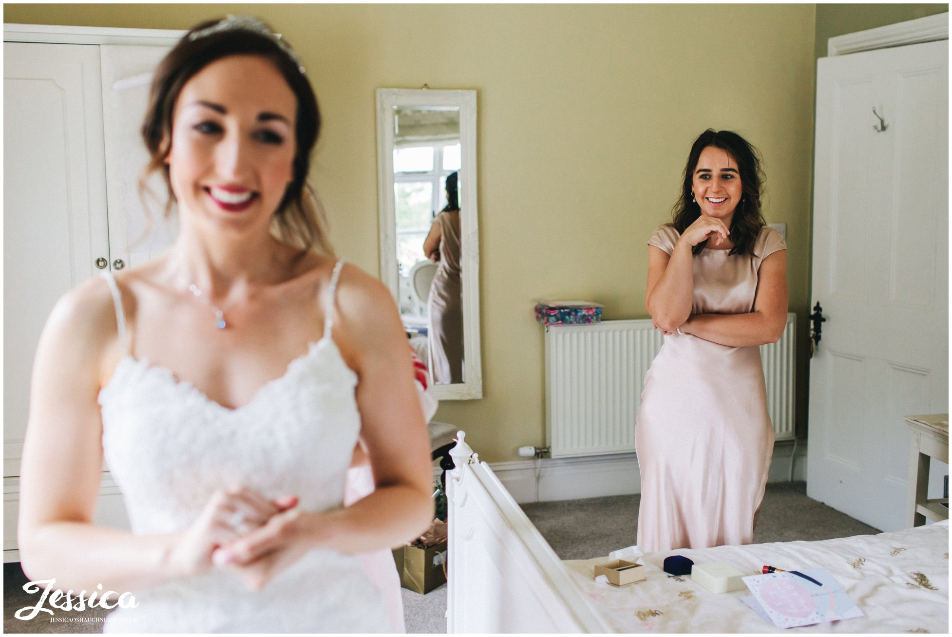 bridesmaid admires her sister in her wedding dress