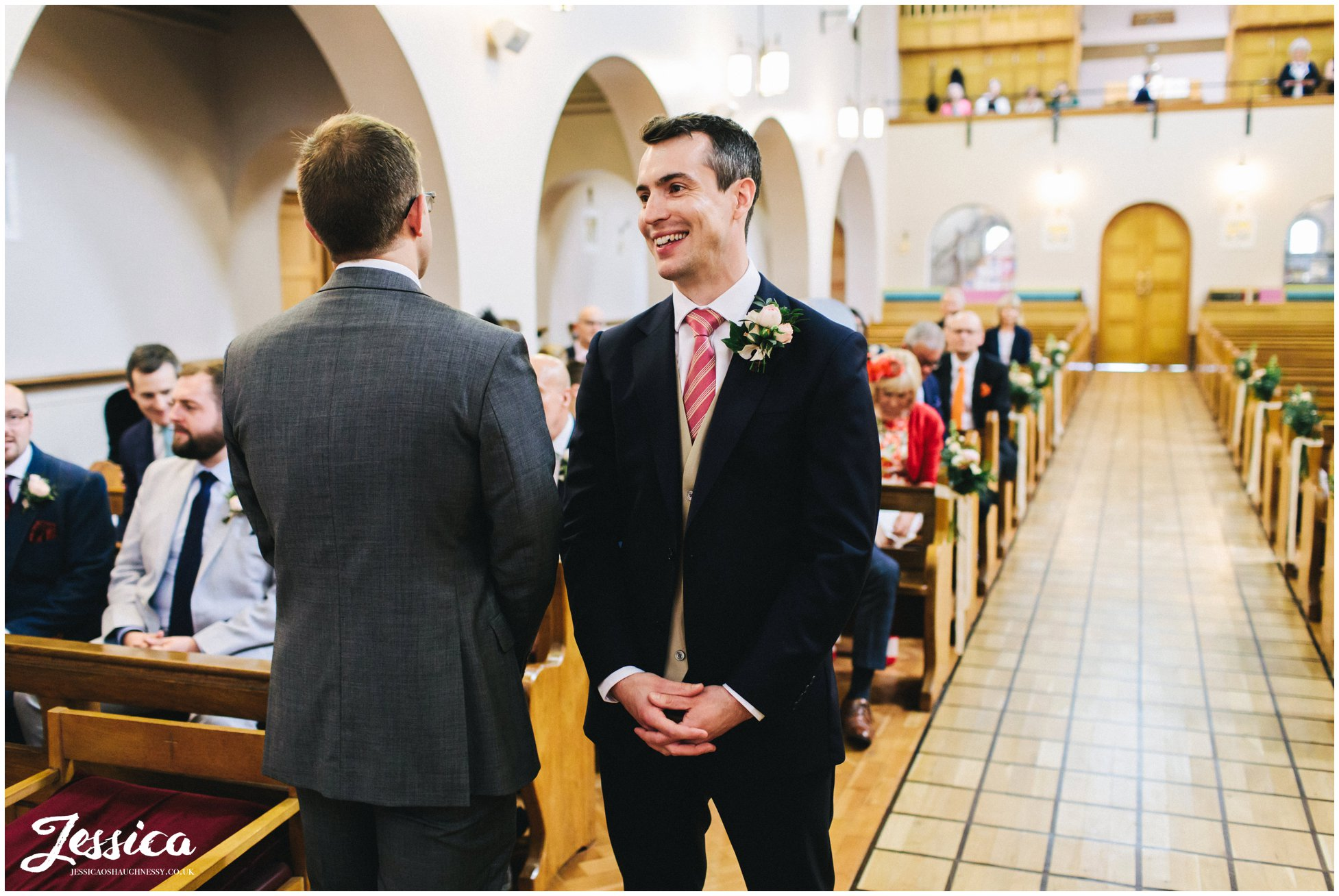 groom happily waits at the alter for his bride