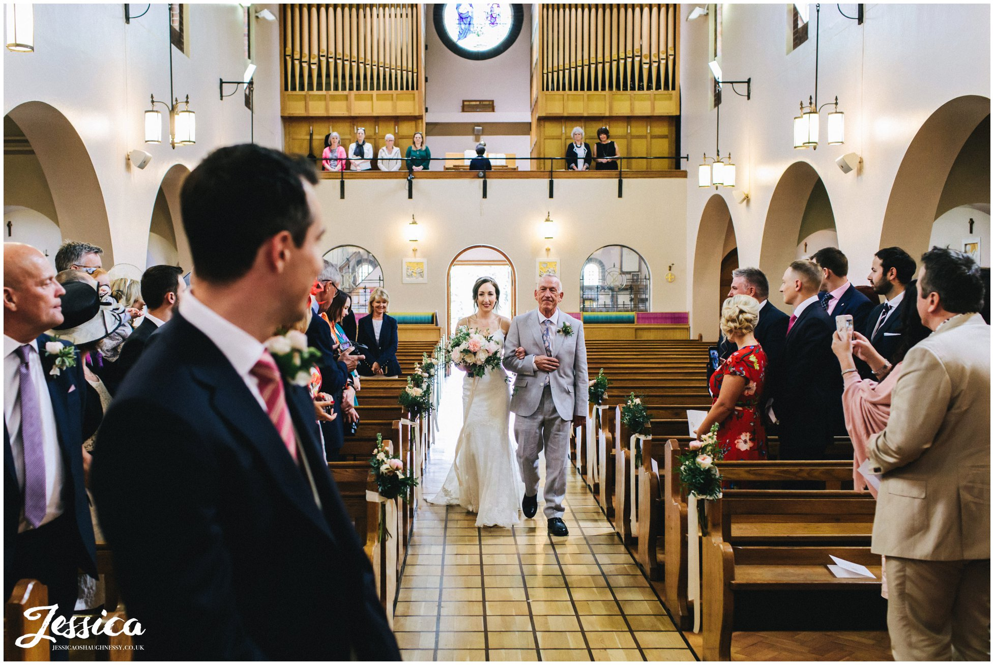 bride walks down the aisle at wirral church