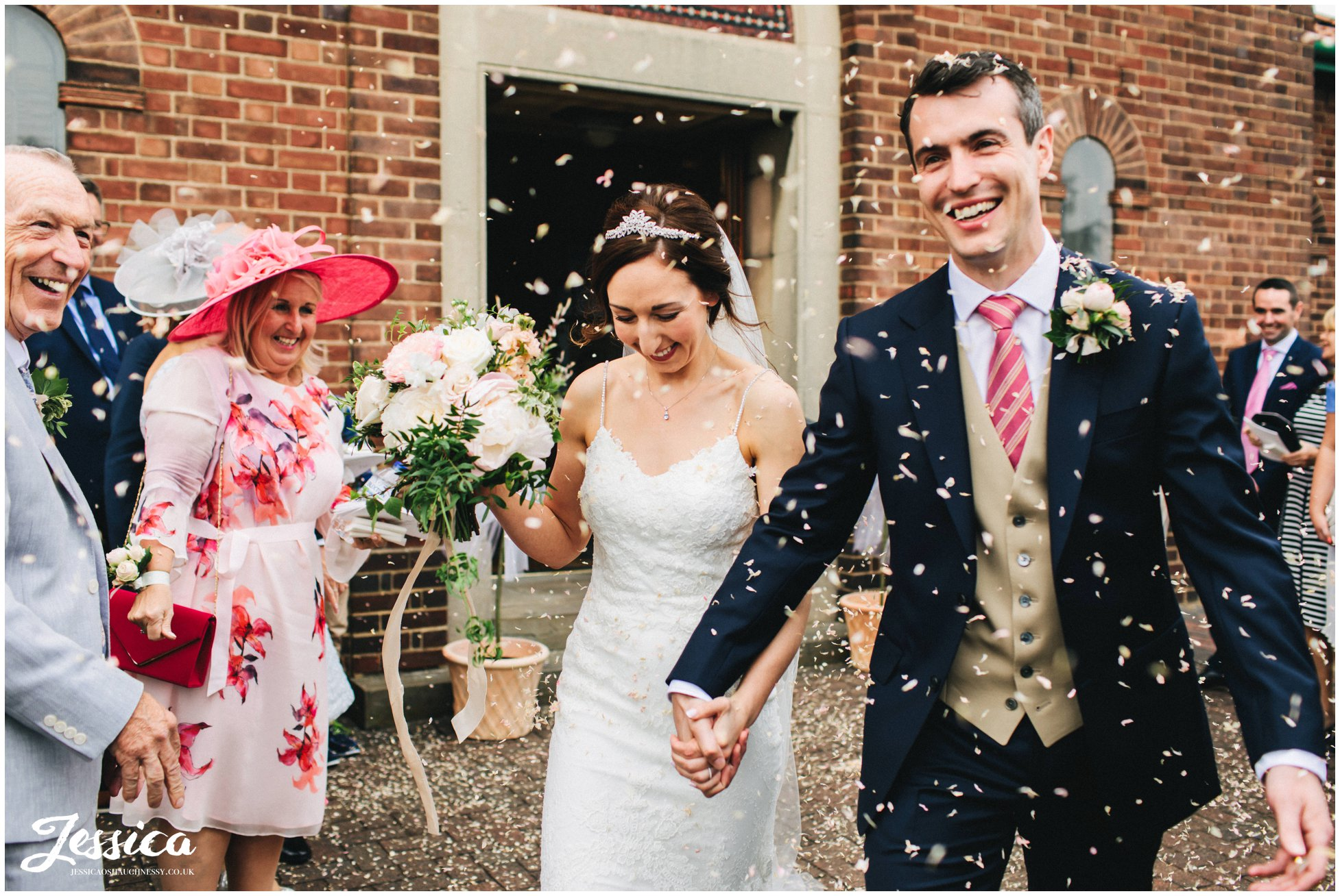 the bride and groom are showered in confetti at their wirral wedding