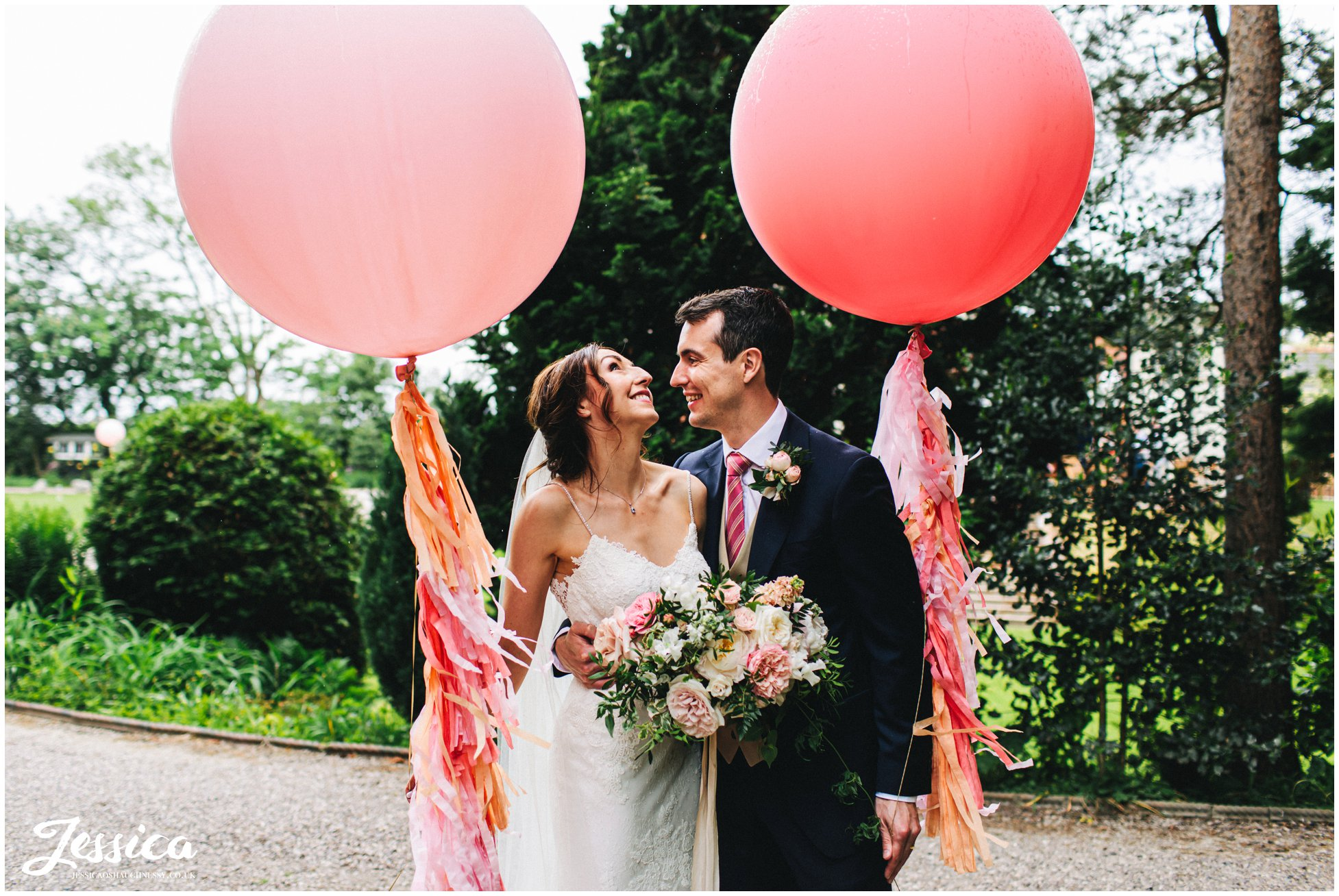 newly wed's pose with giant pink balloons