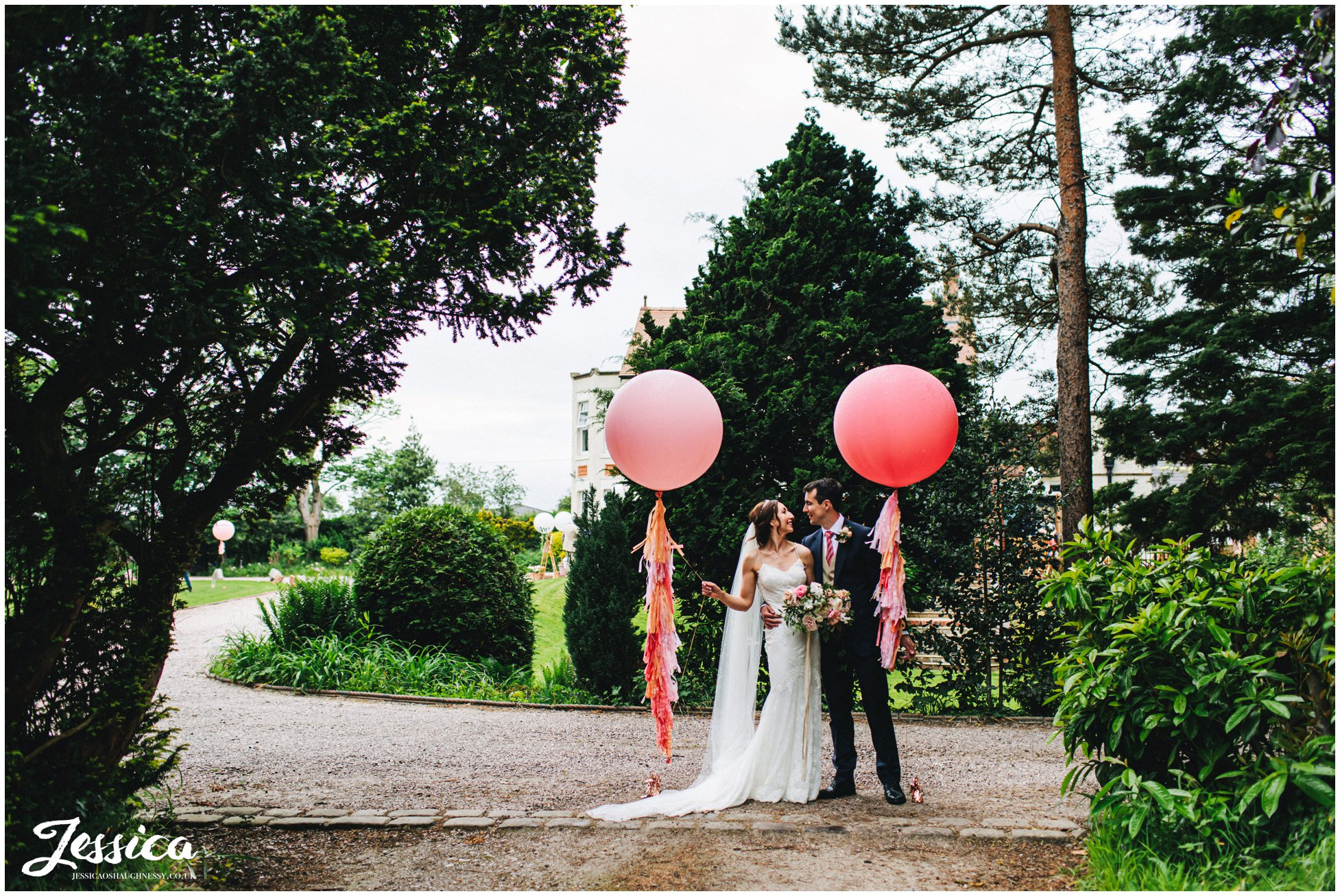 couple stand with giant balloons at mere brook house