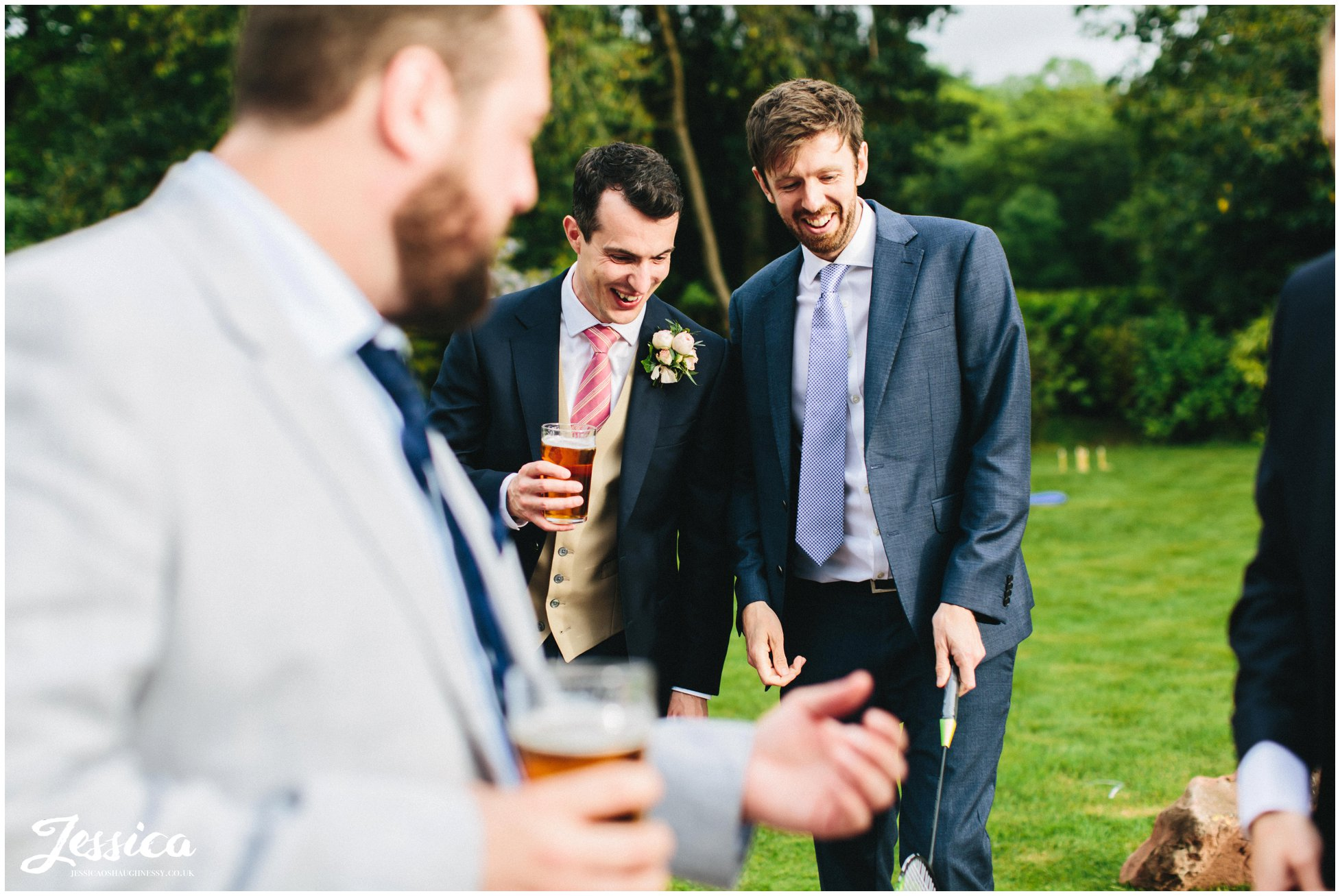 groom jokes with friends in the venue gardens