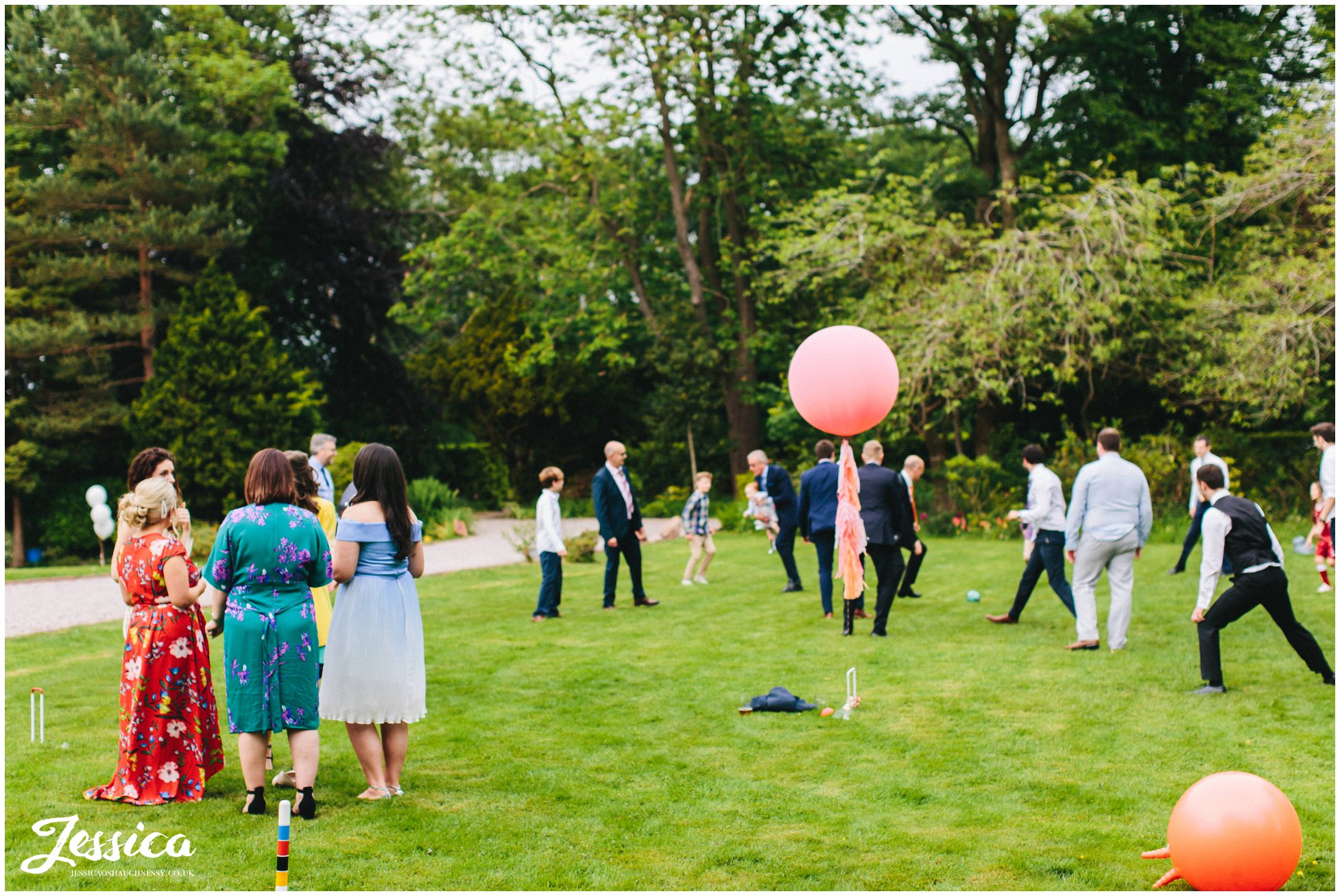 men play football and the women watch at mere brook house wedding