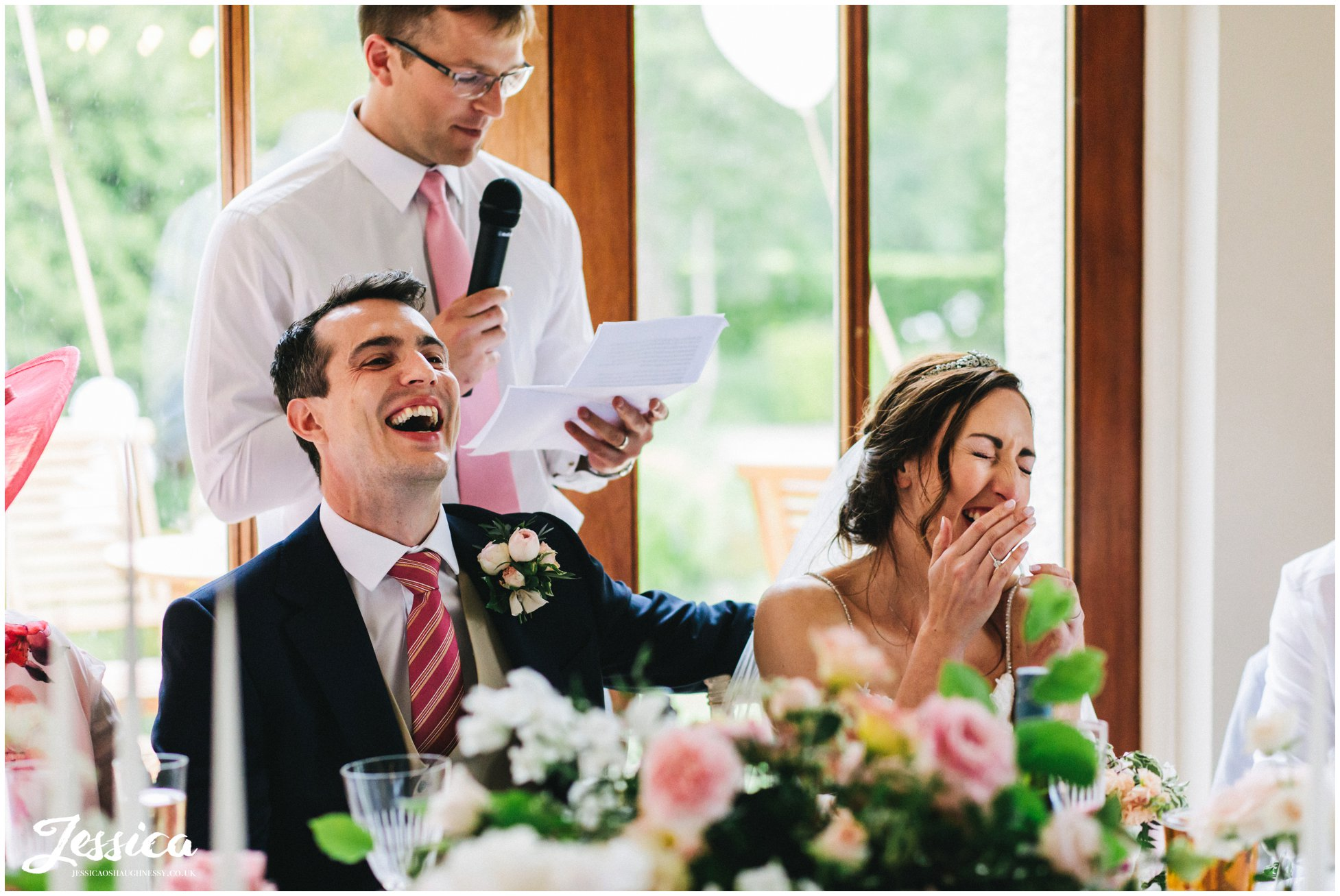 bride & groom laugh at the best man's speech