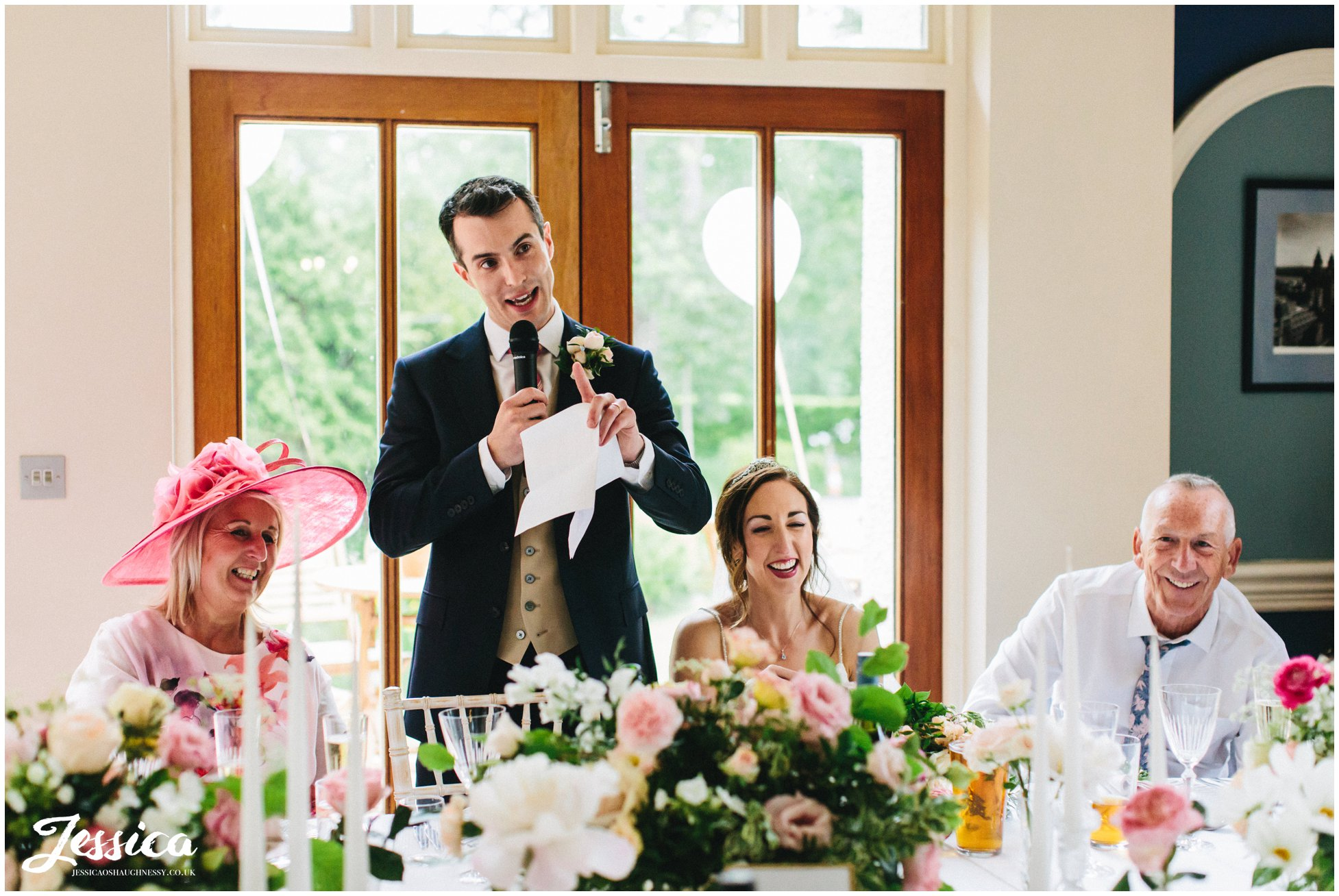 groom stands to deliver his speech