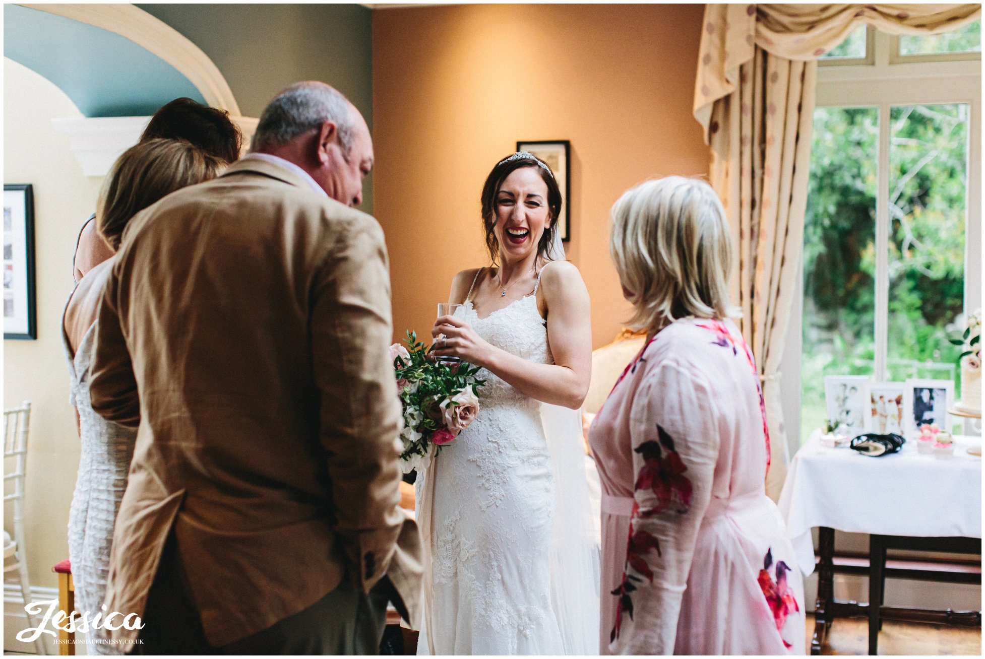 bride laughs with wedding guests at the evening reception