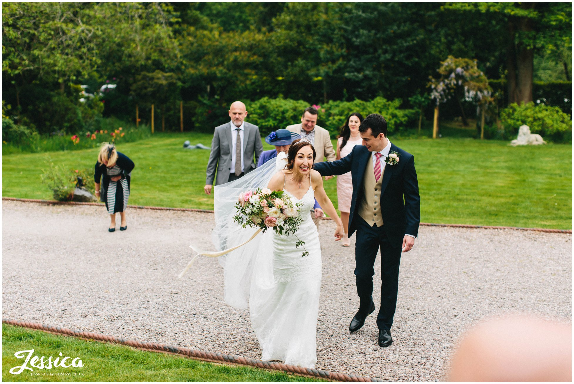 bride excitedly greets guests at mere brook house