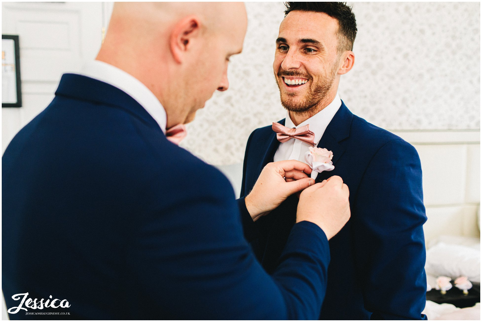 best man helps groom put on his button hole