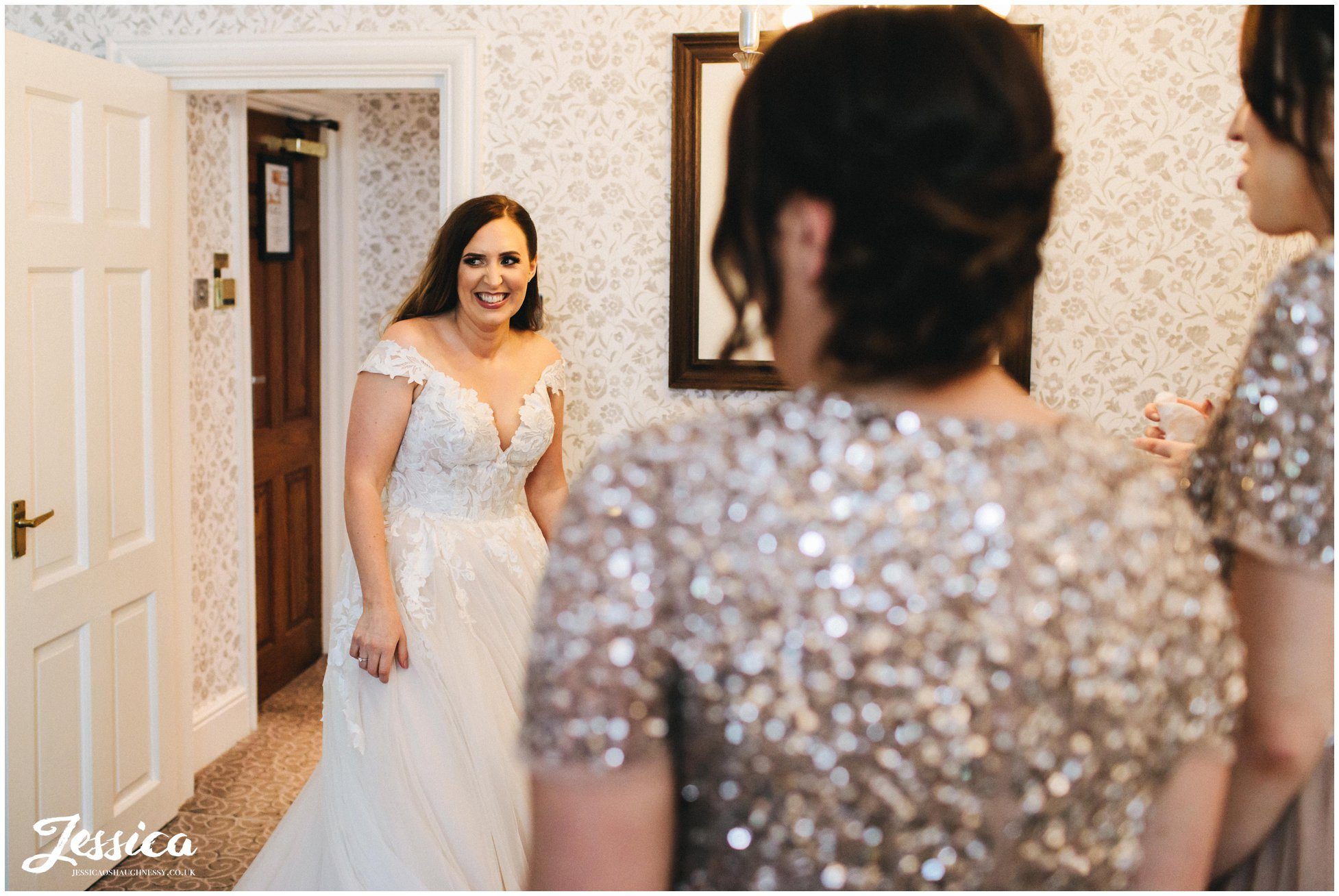 bride walks in to show her bridesmaids her wedding dress