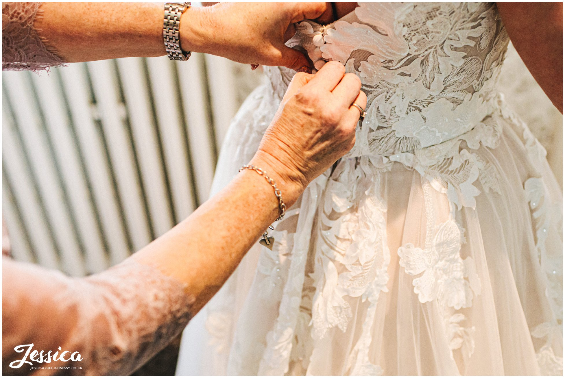 bride has dress buttoned up by her mum before the ceremony