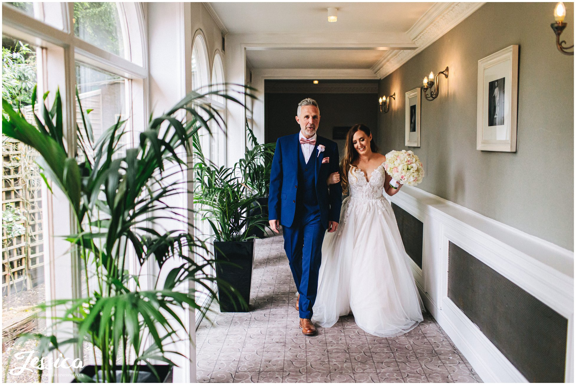 bride & father walk down mottram hall corridor to the ceremony