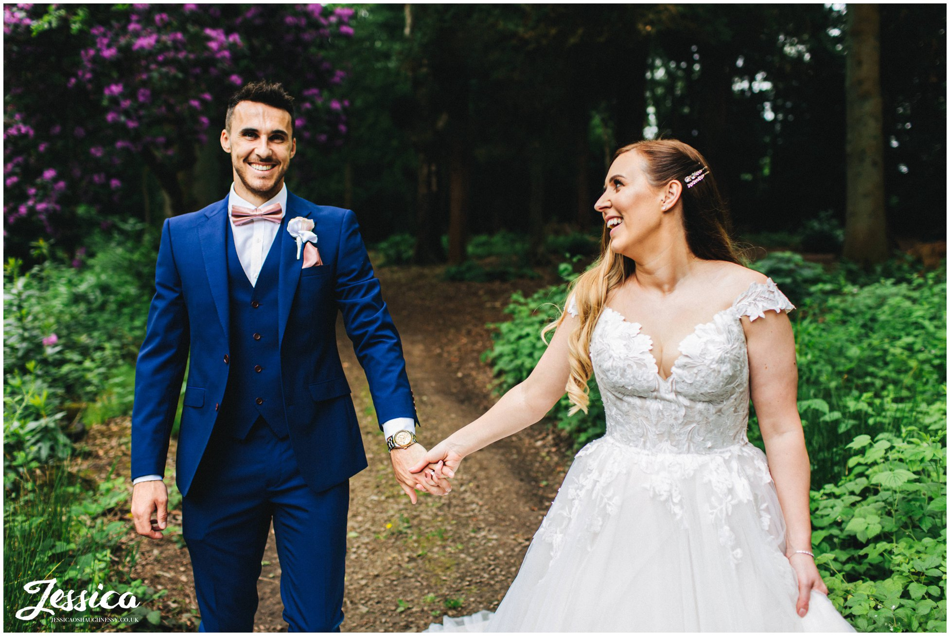 bride takes grooms hand as they walk through the woods