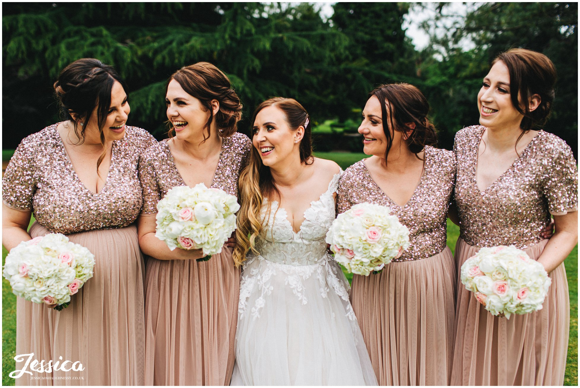 bride & bridesmaids laugh together in the venue gardens