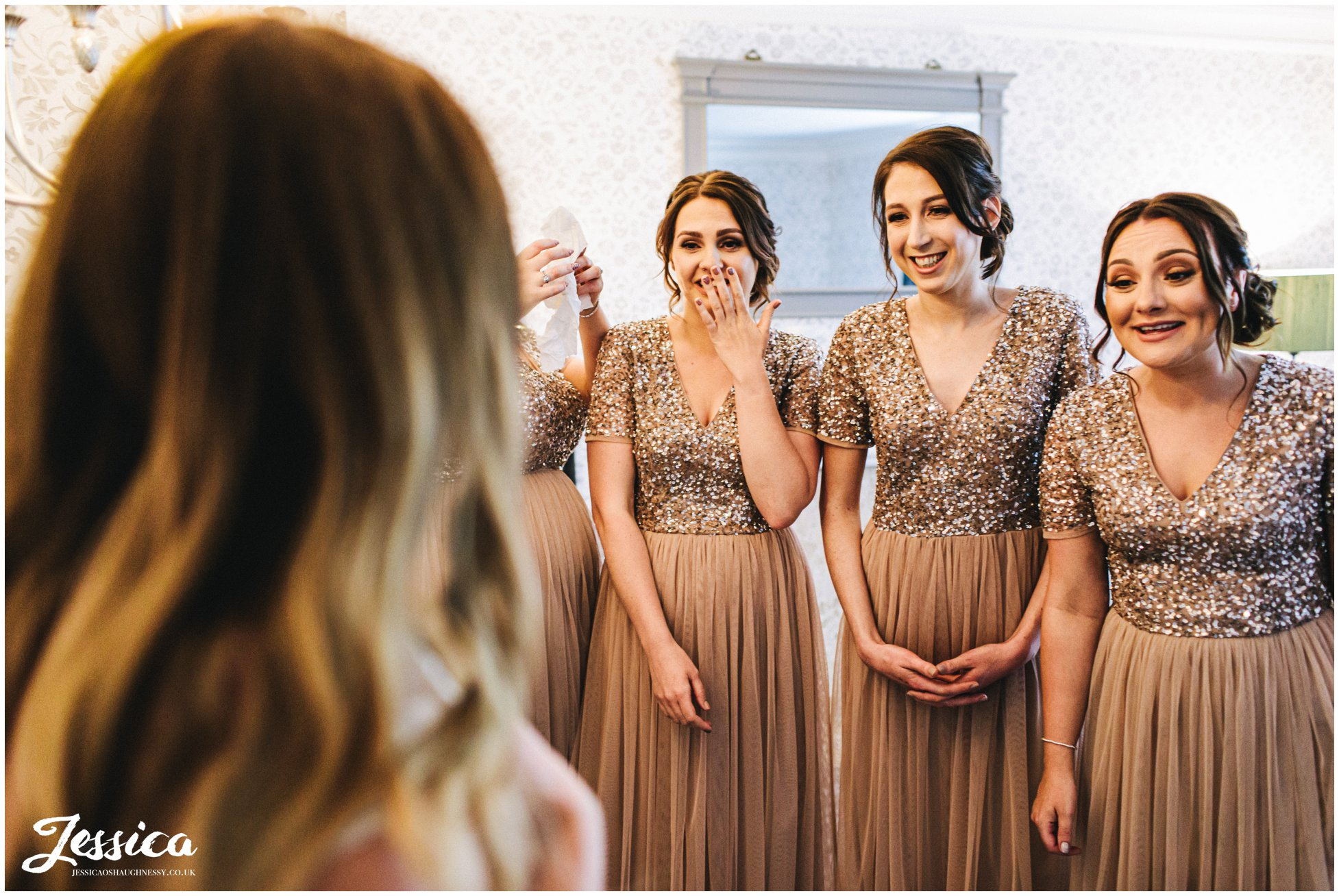 bridesmaids get emotional as they see the bride in her dress