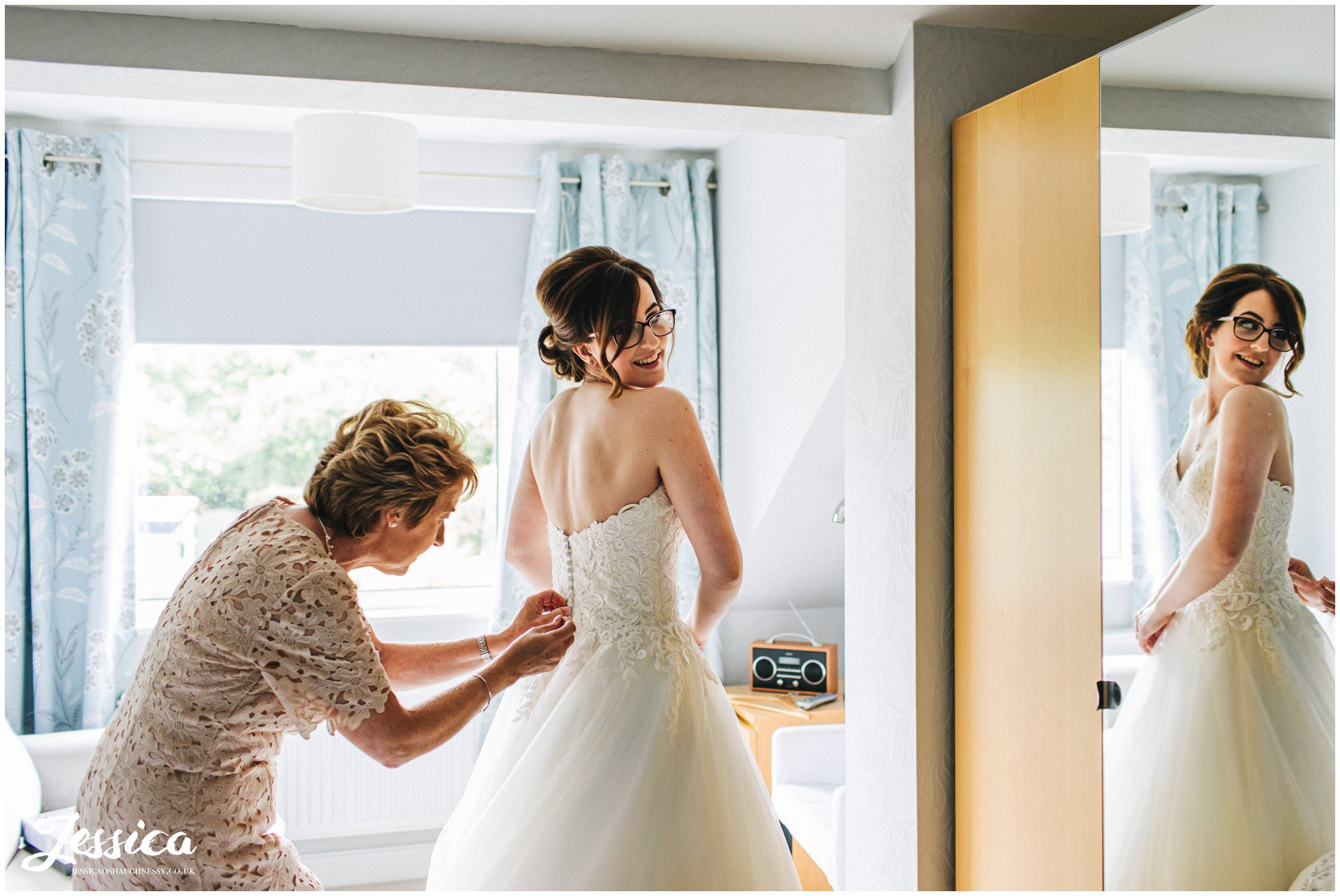 Mother of the bride fastens the wedding dress on her daughter