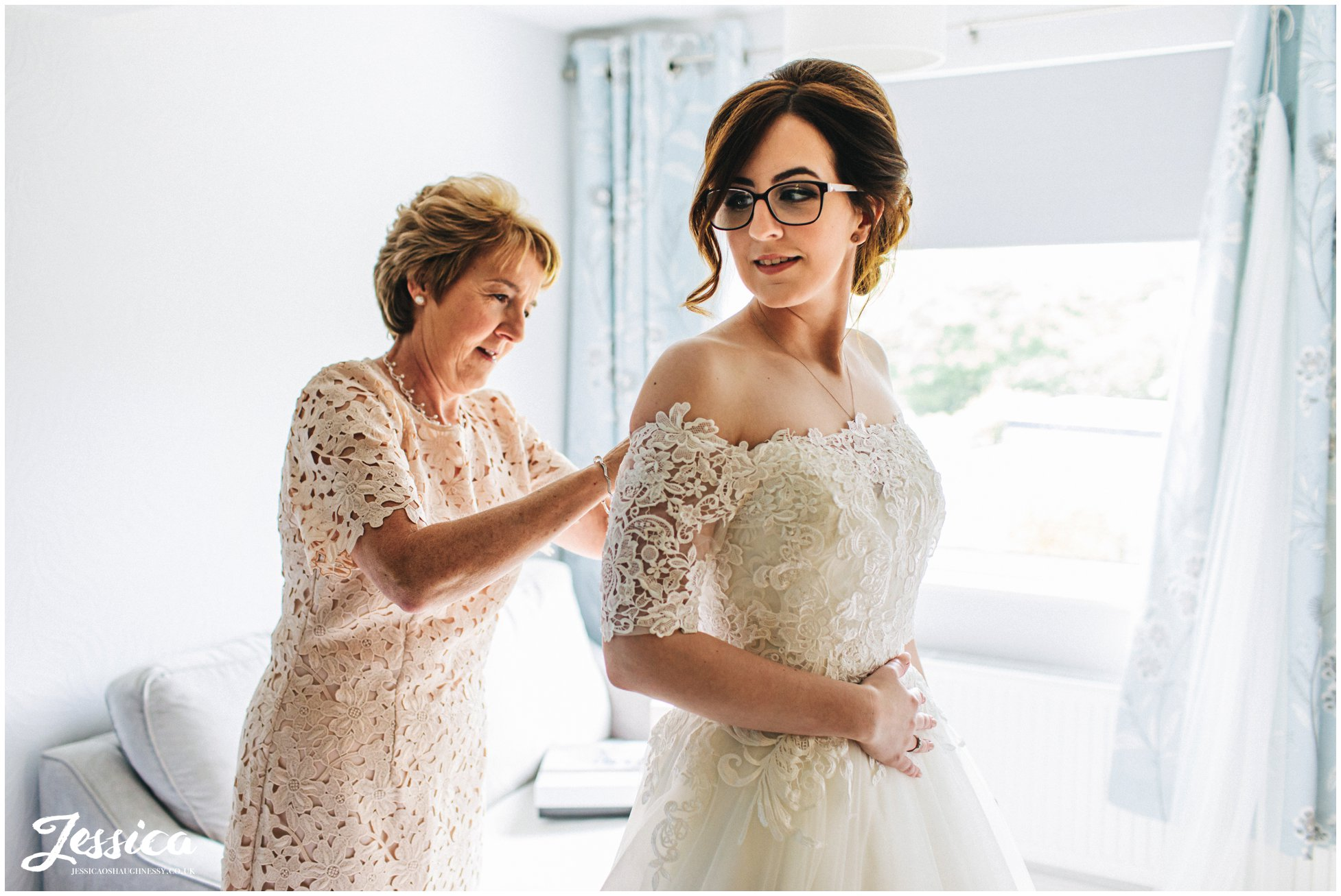 Bride gets into her wedding dress before the north wales wedding
