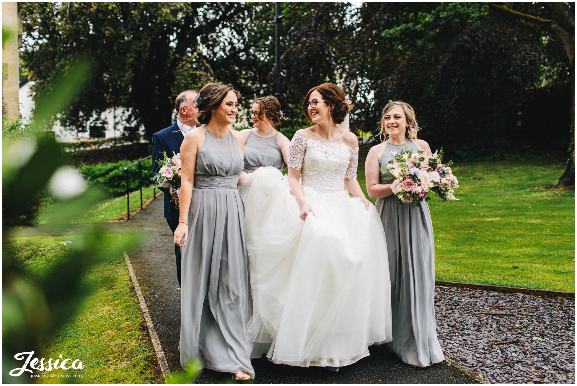 bridesmaids carry the brides dress down the church path