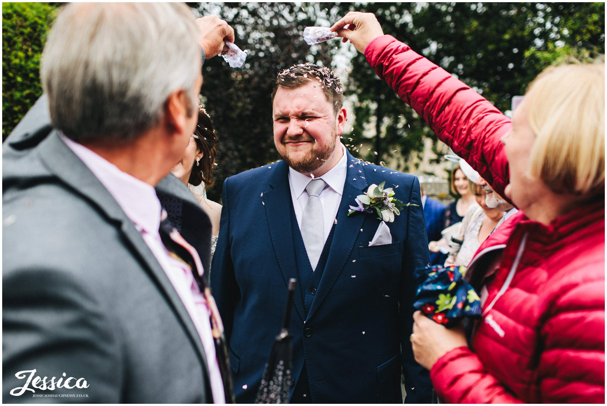 wedding guests throw confetti over the grooms head