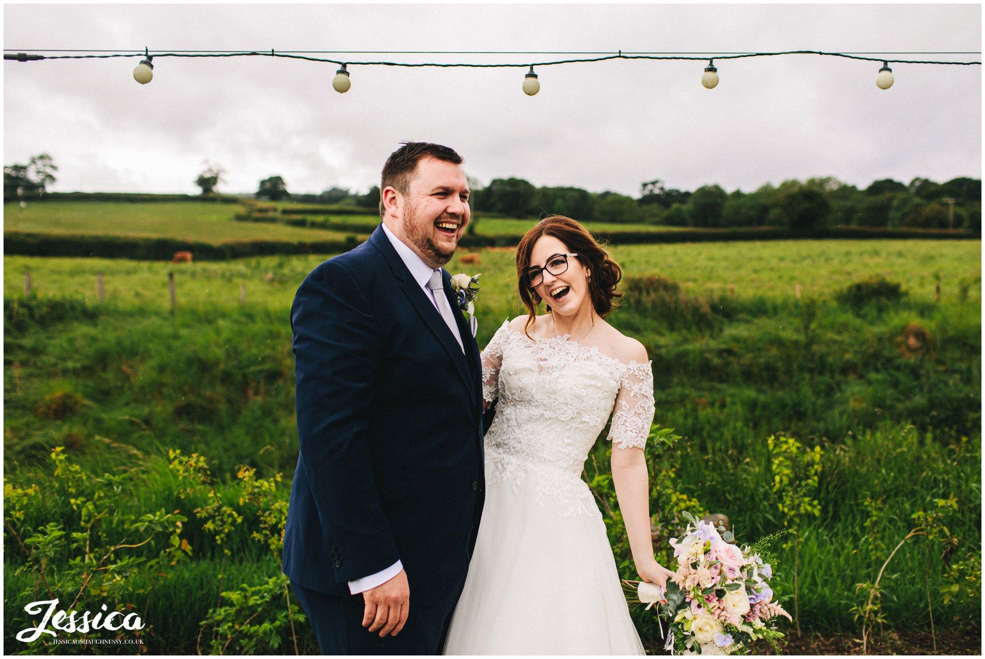 couple laugh under festoon lighting