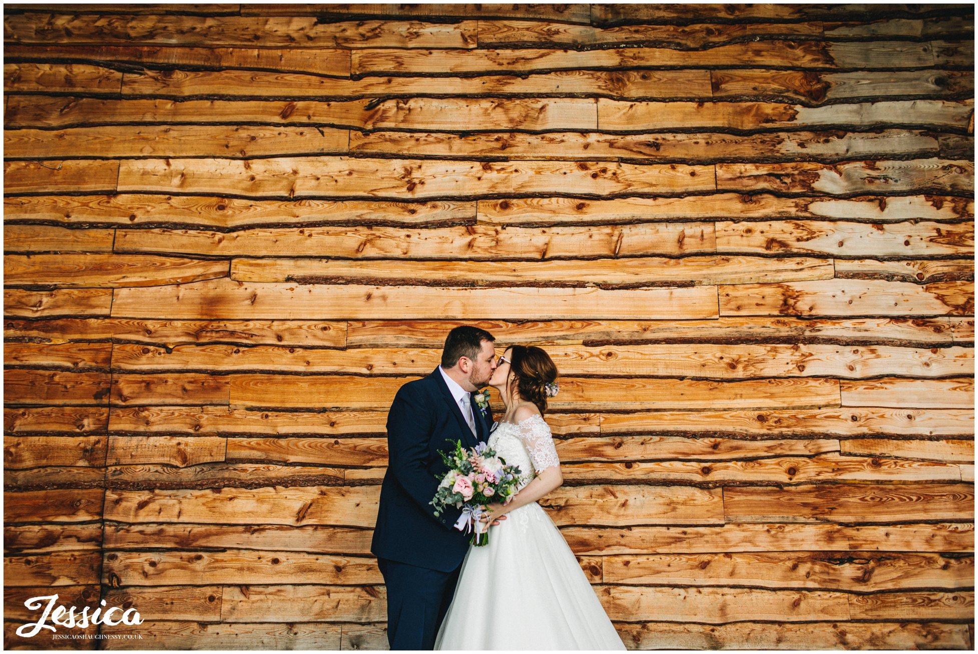 couple kiss under tower hill barns bridge