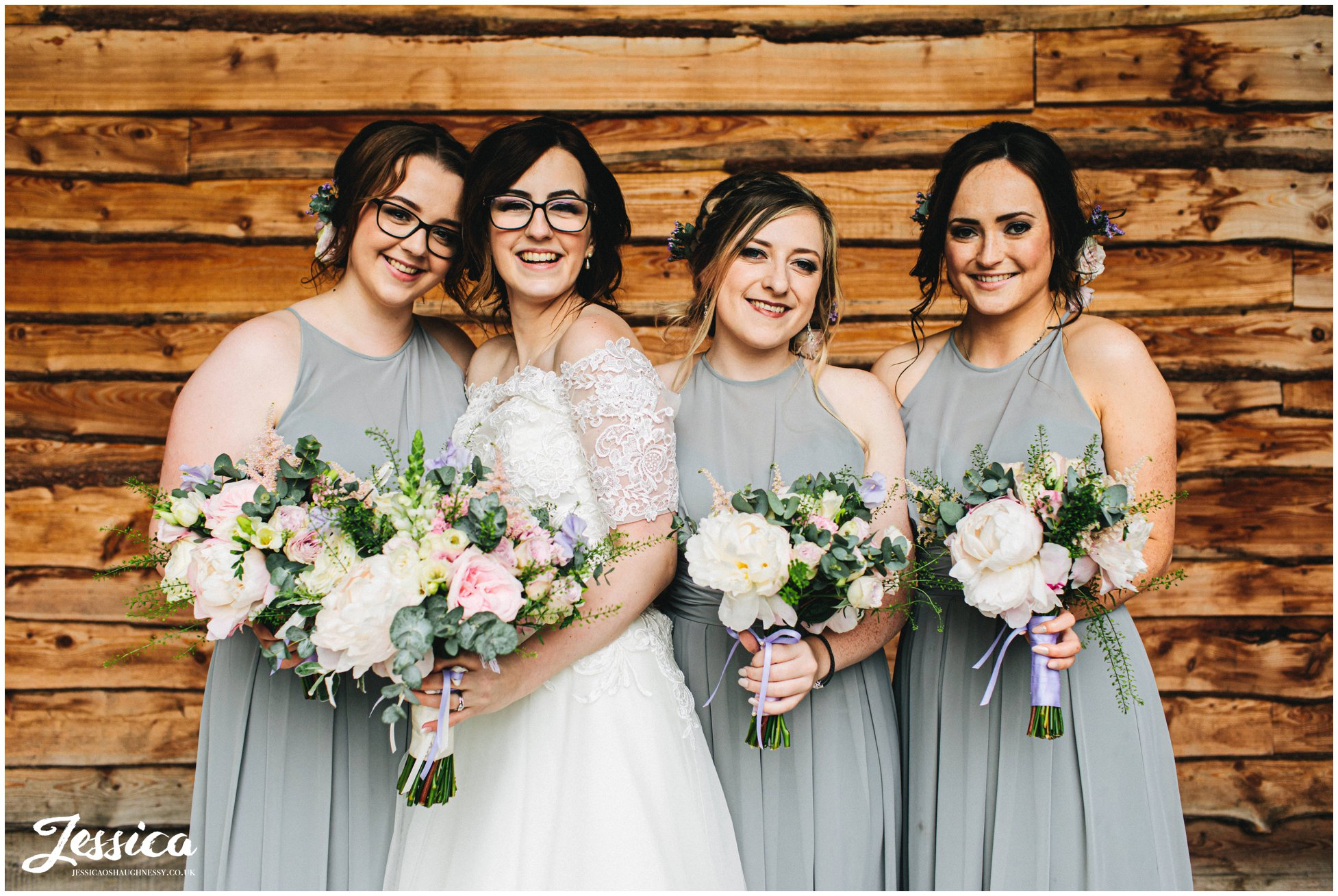 bride poses with her bridesmaids at tower hill barns