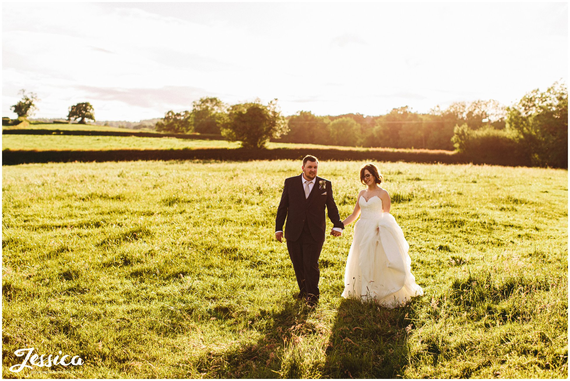 husband and wife walk through fields surrounding the north wales wedding venue