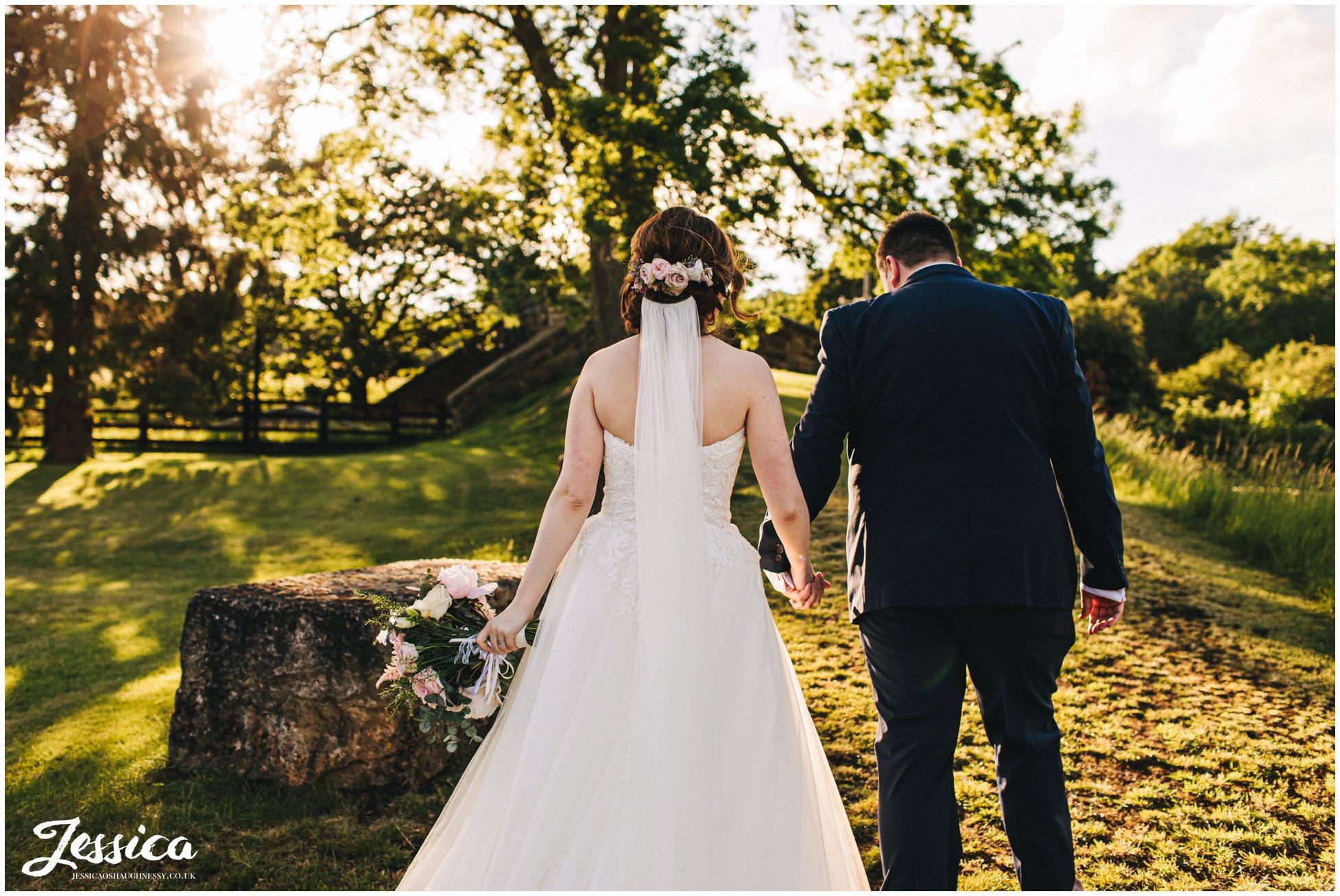 bride walks away with flowers in her hair