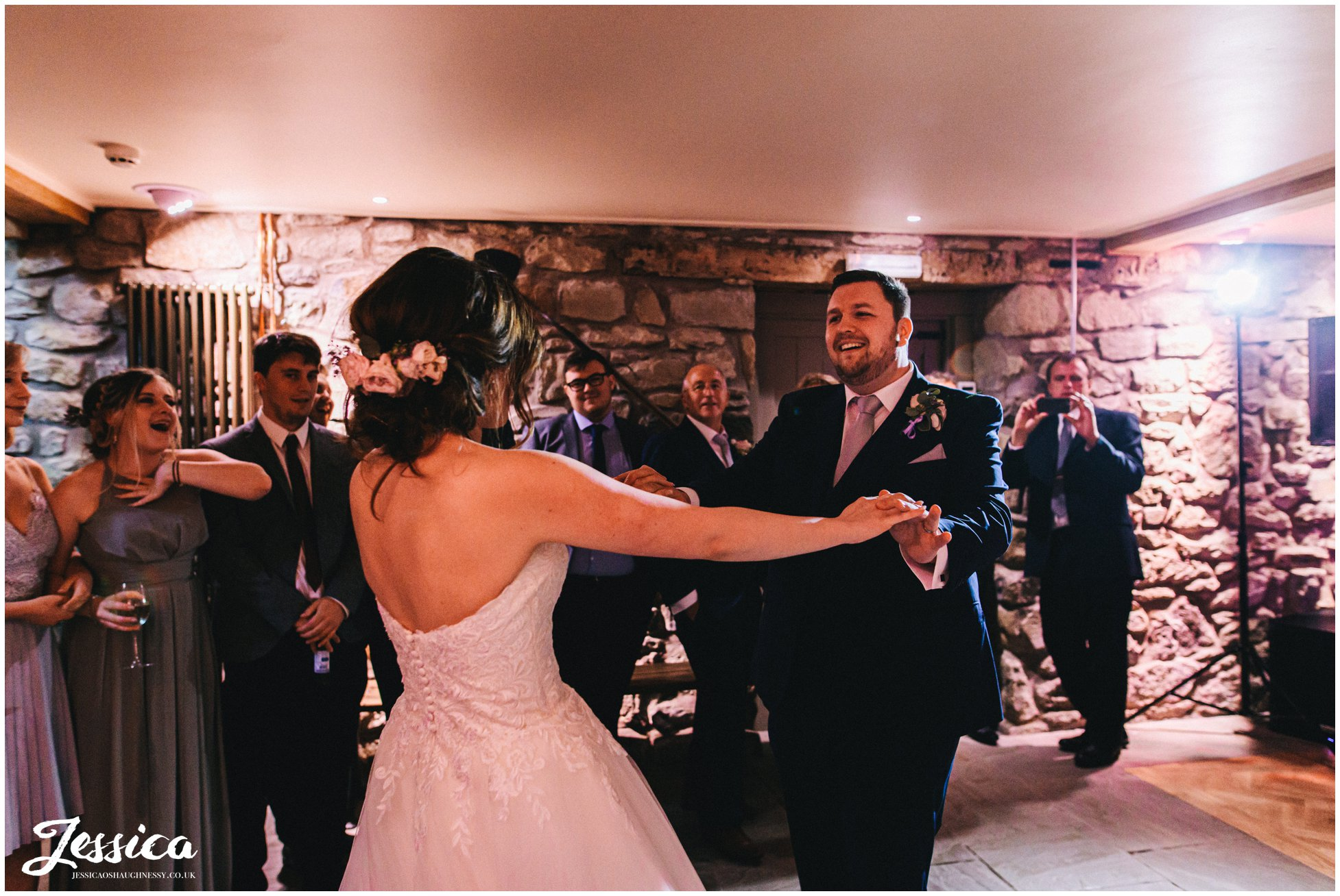 couple share their first dance in the old barn