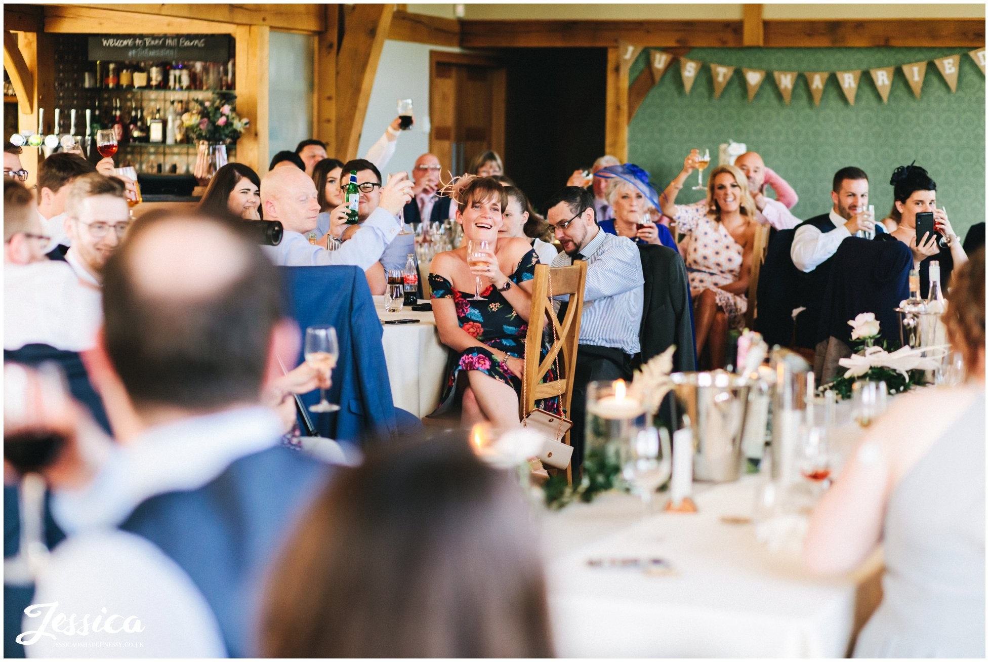 wedding guests laugh during the grooms speech