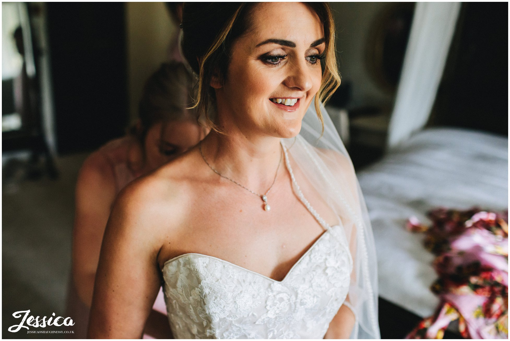 bride smiles as her dress is fastened by her bridesmaids